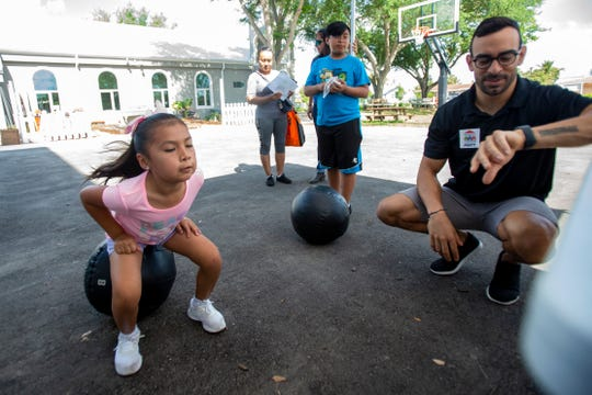 Matt Torres, owner of North Naples Cross Fit counts the number of squats Carla Garcia, 7, can do in 60-seconds during a fitness challenge during Family Literacy Day, Saturday, April 6, 2019, at Grace Place in Golden Gate. At center, Christopher Sanchez, 11, waits for his turn to take part in the squat challenge.