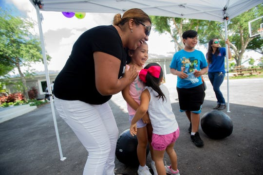 Carla Garcia, 7, gets a hug from her mother Bernice Garcia and sister Vanessa Garcia after Carla received a high score during the squat challenge during Family Literacy Day, Saturday, April 6, 2019, at Grace Place in Golden Gate.