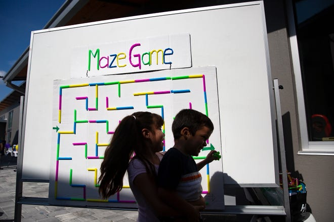 Gracie Reséndiz, 6, carries Manuel Salazar ,4, while playing with a maze during Family Literacy Day, Saturday, April 6, 2019, at Grace Place in Golden Gate.