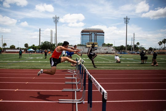Athletes jump over hurdles at the Collier County Athletic Conference track and field meet at Naples High School on Saturday.