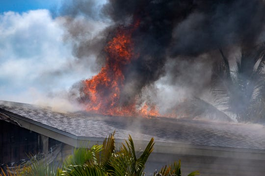 Flames leaps from the roof of a home, Saturday, April 6, 2019,  at the 800 block of 94th Avenue North in the Naples Park Community in North Naples.