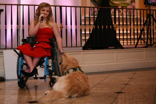 Erin Bischoff with her service dog Gauge, performs a song at Il Villaggio during a fundraiser for Mickey's Kids Foundation for service dogs in Carlstadt on Friday April 5, 2019. Bischoff recently played Dorothy and Gauge played Toto in her High School production of Wizard of Oz.