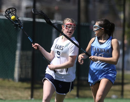 Reilly Brown of Ramsey carries the ball while being defended by Jordan Aronson of Mahwah in the second half.