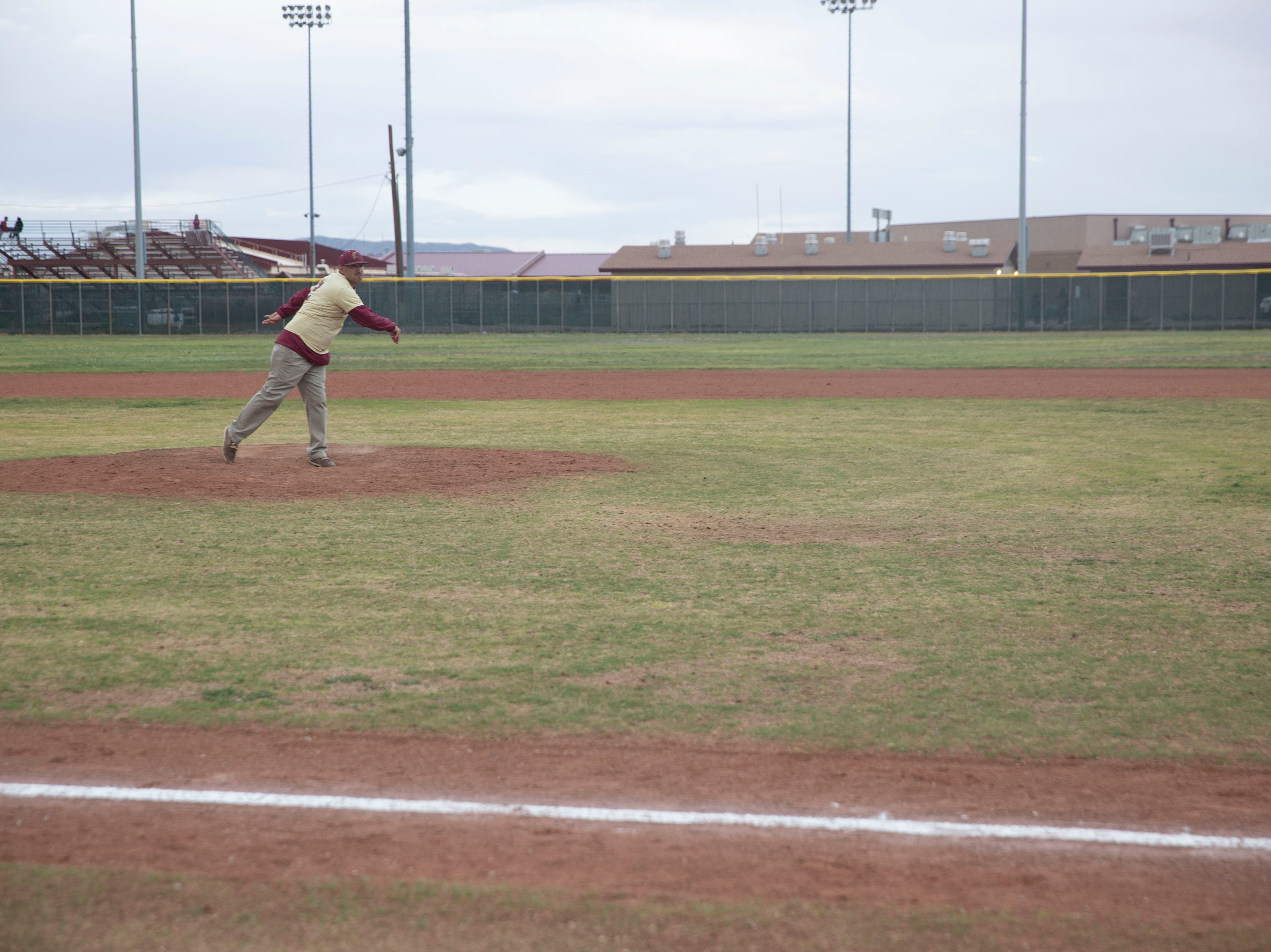 Beto Romero Sr. throws the first pitch at a baseball game Friday, April 5, in honor of his son Beto Romero Jr., 16, who was killed this week in a hit-and-run accident.