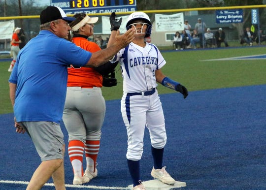 Marissa Reyes high-fives Carlsbad head coach John Tigert after she hit a triple in the sixth inning to give Carlsbad a 5-1 lead over Artesia.