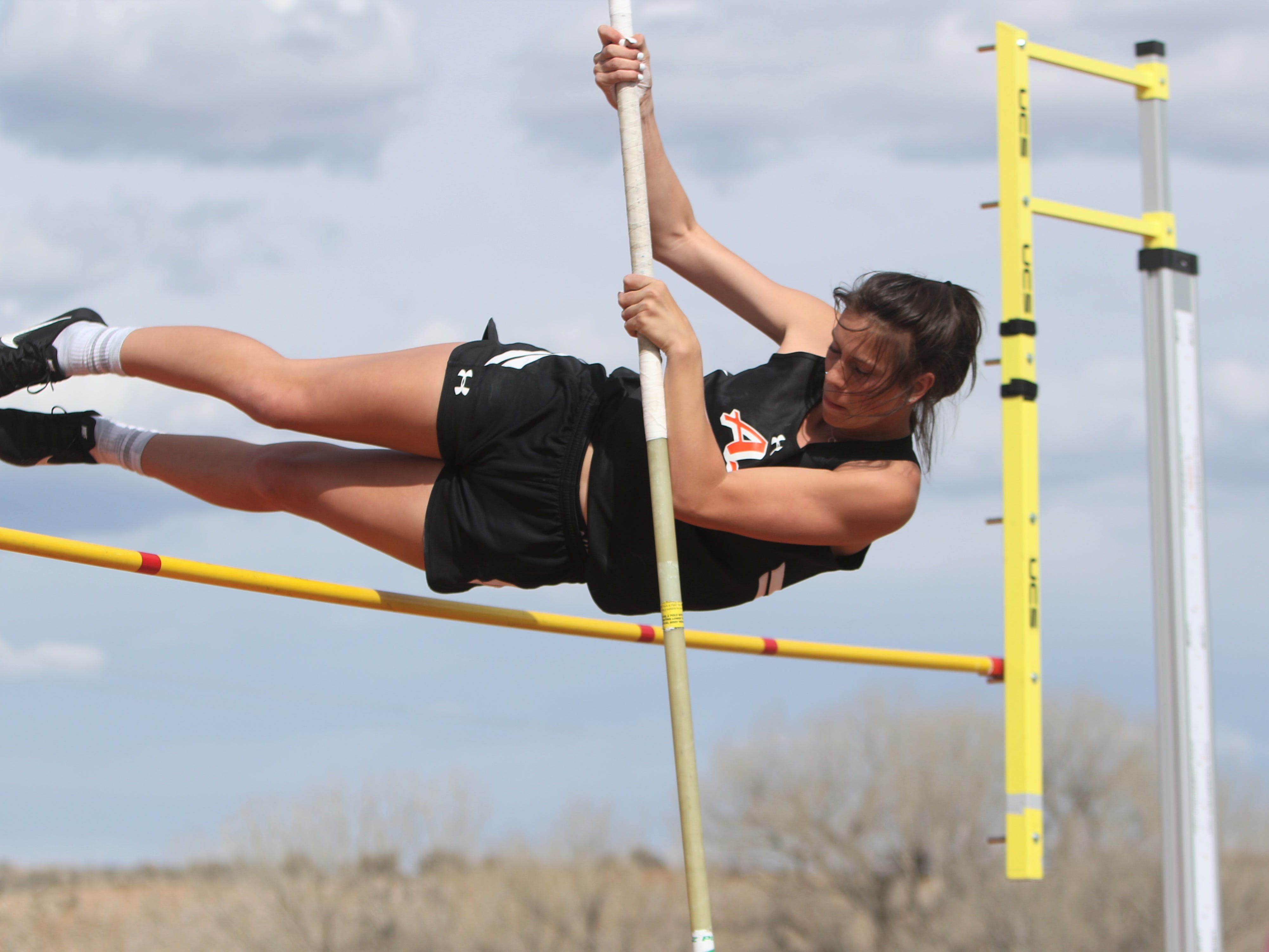 Aztec's Carley Smith successfully catapults herself over the bar in the girls pole vault during Friday's Top Gun Invitational at Aztec.