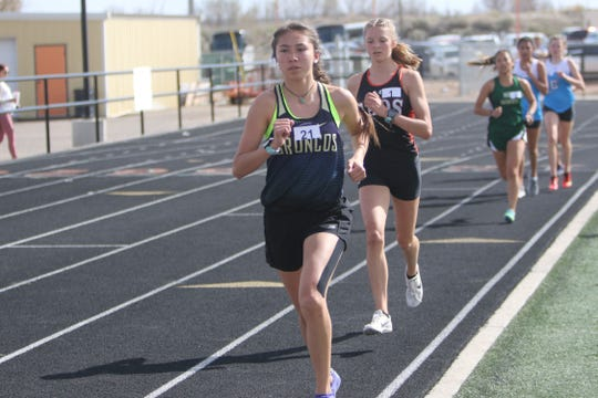 Kirtland Central's LaKyla Yazzie takes the lead in the third lap of the girls 3,200-meter run during Friday's Top Gun Invitational at Aztec. Yazzie won the race and qualified for state in that event.