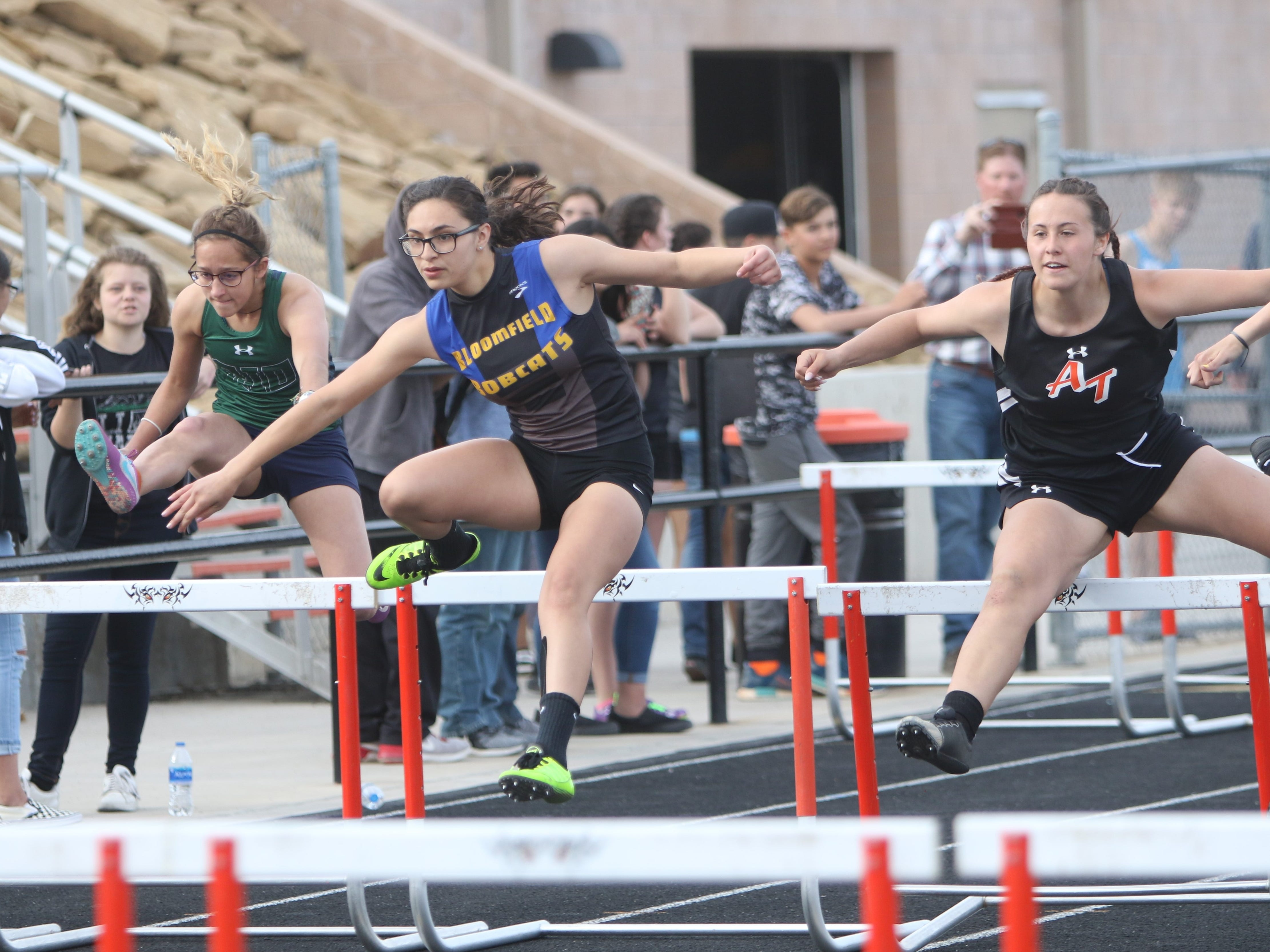 Bloomfield's Lylie Nunez keeps pace with Aztec's Helen Moore (right) with the group in the third heat of the girls 100-meter hurdles during Friday's Top Gun Invitational at Aztec. Moore placed sixth in 17.62 seconds, while Nunez tied for seventh with Taos' Abigail Gunther in 17.70 seconds.