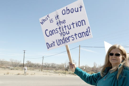 Connie Snell holds a sign, Saturday, April 6, 2019, during a rally in Aztec.