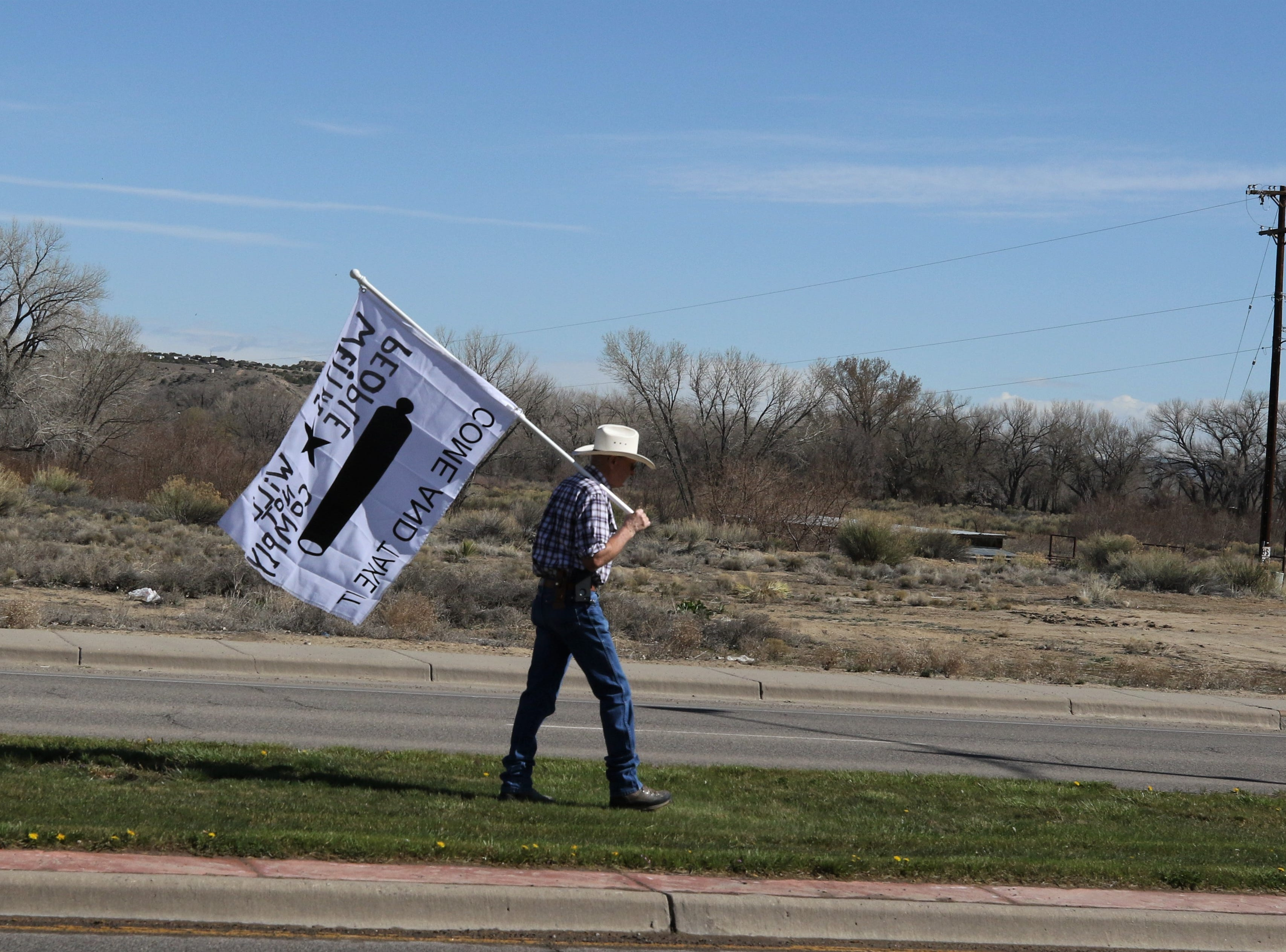 Greg Graves carries a banner in the median of West Aztec Boulevard, Saturday, April 6, 2019, during a Second Amendment rally in Aztec.