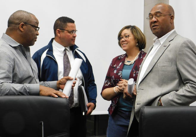 St. Landry Parish Council members Jerry Red, Jr., Dexter Brown and Jimmie Edwards speak with council clerk Sherell Jordan after a meeting.