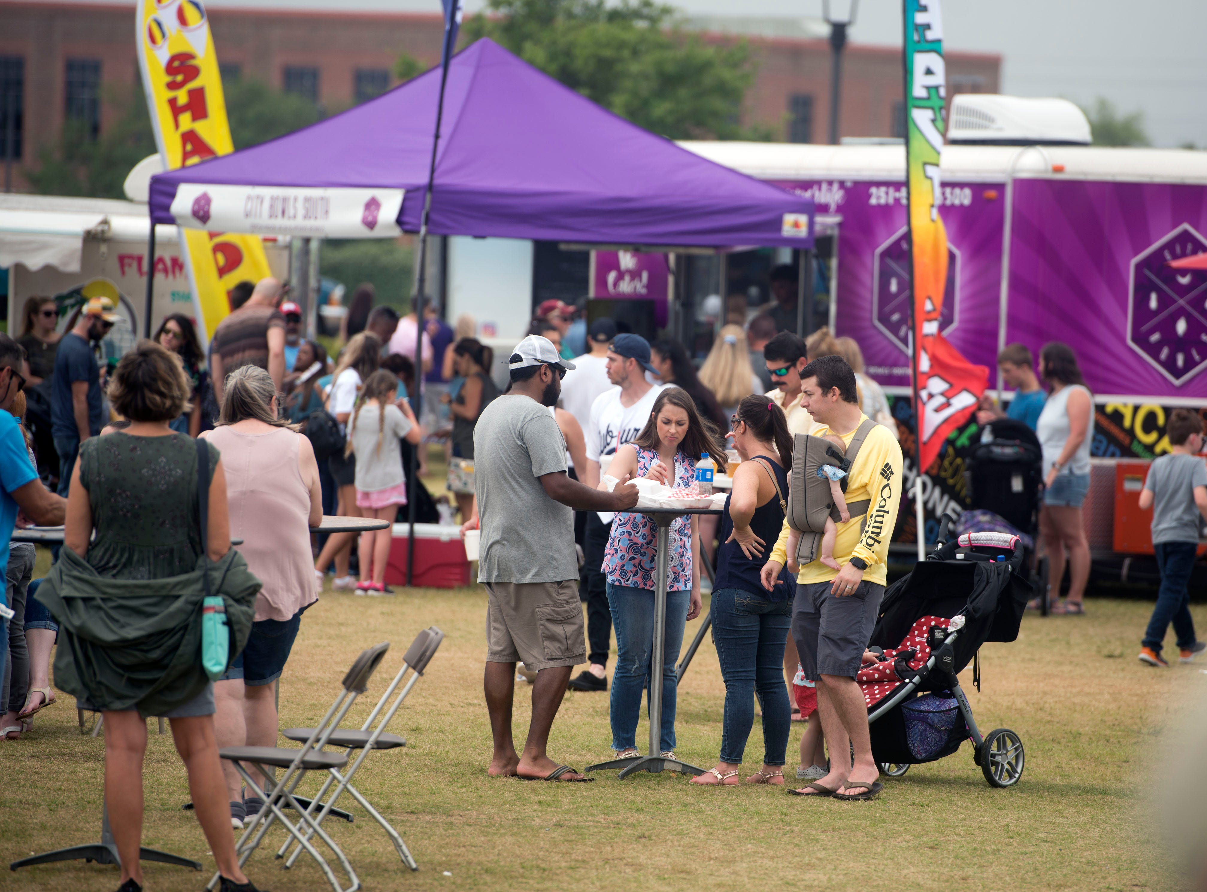 Foodies and families take in the many food choices Saturday, April 6, 2019 during the Pensacola Habitat for Humanity's fourth annual Food Truck Festival at Community Maritime Park.