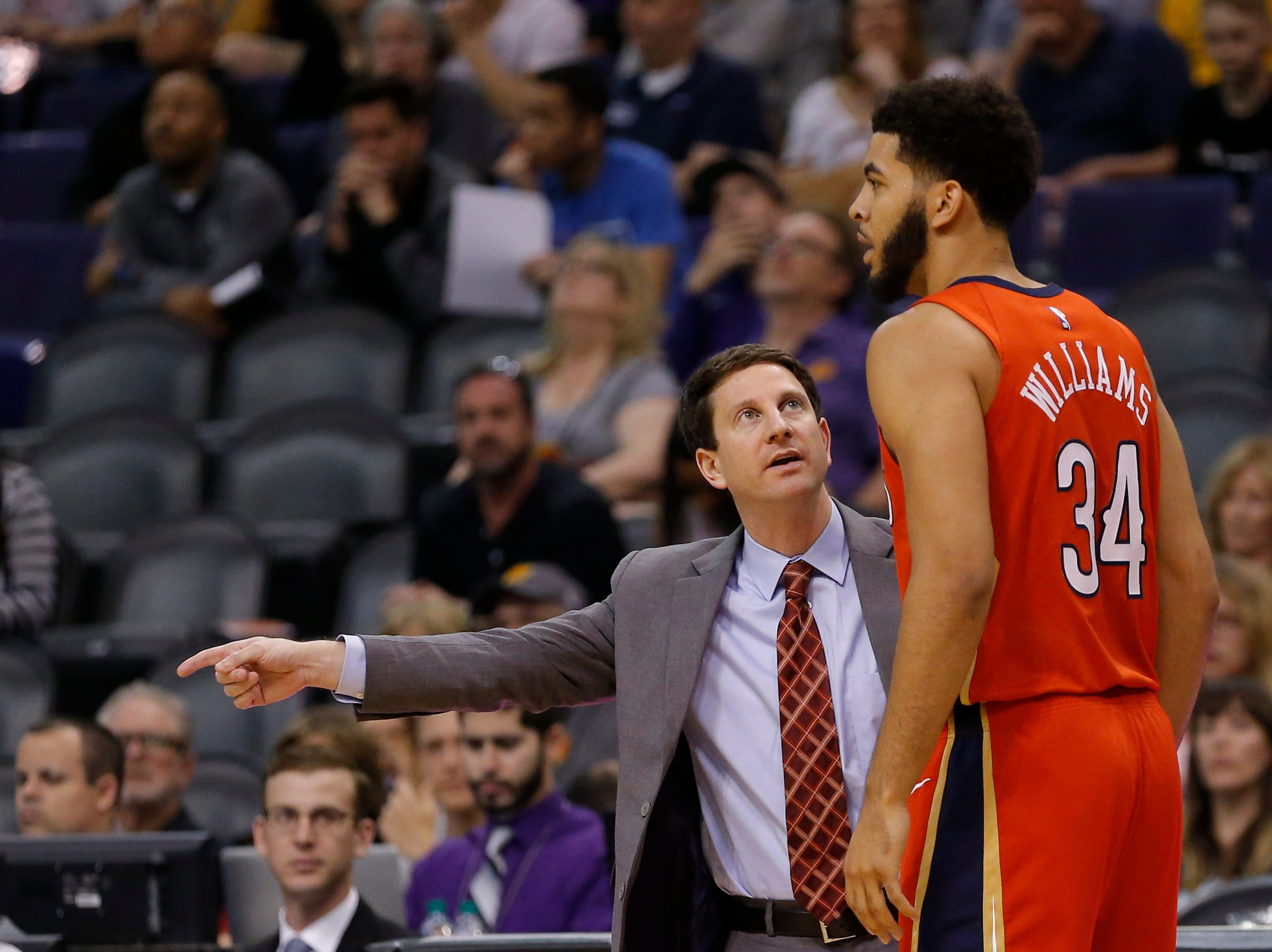 New Orleans Pelicans head coach Alvin Gentry talks with Kenrich Williams (34) in the first half during an NBA basketball game against the Phoenix Suns, Friday, April 5, 2019, in Phoenix. (AP Photo/Rick Scuteri)