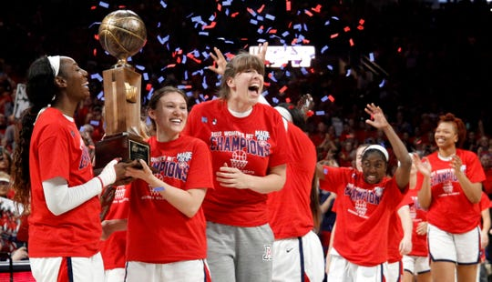 Arizona forward Destiny Graham, guard Lindsey Malecha, Eugenie Simonet-Keller hold the championship trophy as guard Aari McDonald and center Semaj Smith and the team come out onto the court after a win over Northwestern during an NCAA college basketball game for the WNIT championship Saturday, April 6, 2019, in Tucson, Ariz.