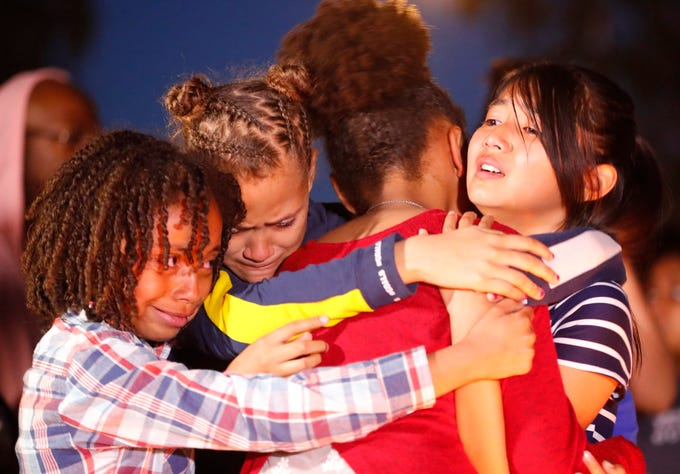Valencia (L-R), Lilly Hernandez and Jazlynn Boungert (R) hug Naima as they cry at a vigil for Summer Bell Brown outside her home where she was shot and killed in Phoenix on April 5, 2019. Brown was their friend and fellow classmate.