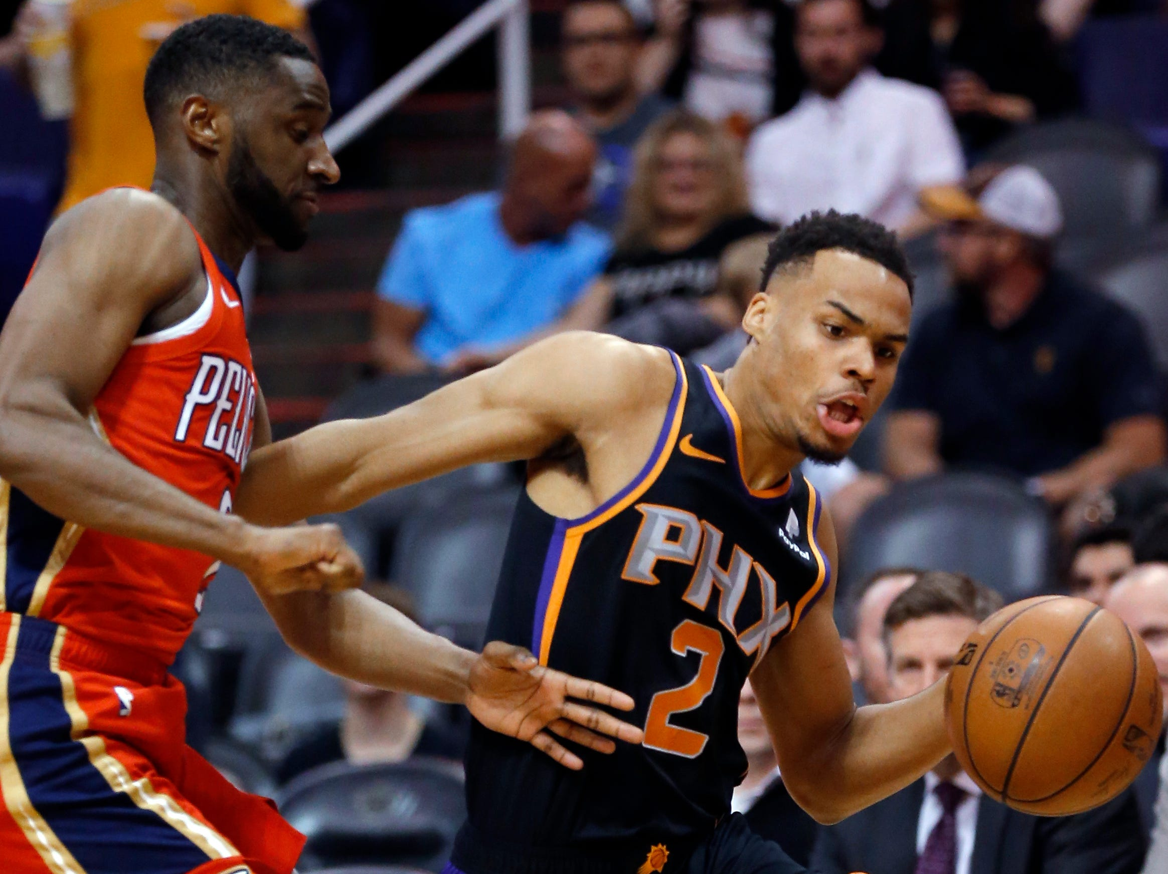 Phoenix Suns guard Elie Okobo (2) drives around New Orleans Pelicans guard Ian Clark during the second half of an NBA basketball game Friday, April 5, 2019, in Phoenix. The Suns won 133-126 in overtime. (AP Photo/Rick Scuteri)