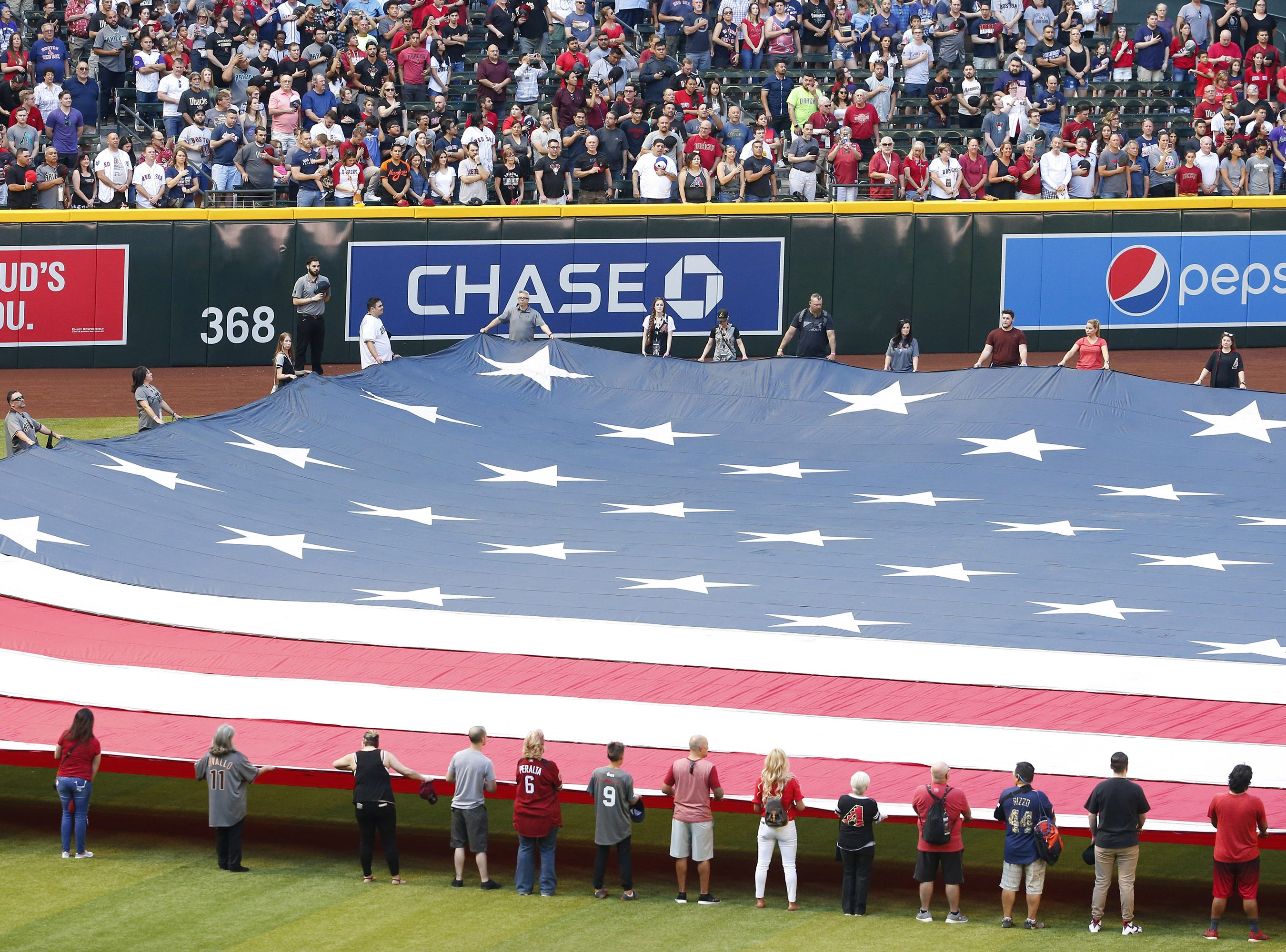 Arizona Diamondbacks fans hold the flag during the National Anthem on Opening Day at Chase Field in Phoenix on April 5.