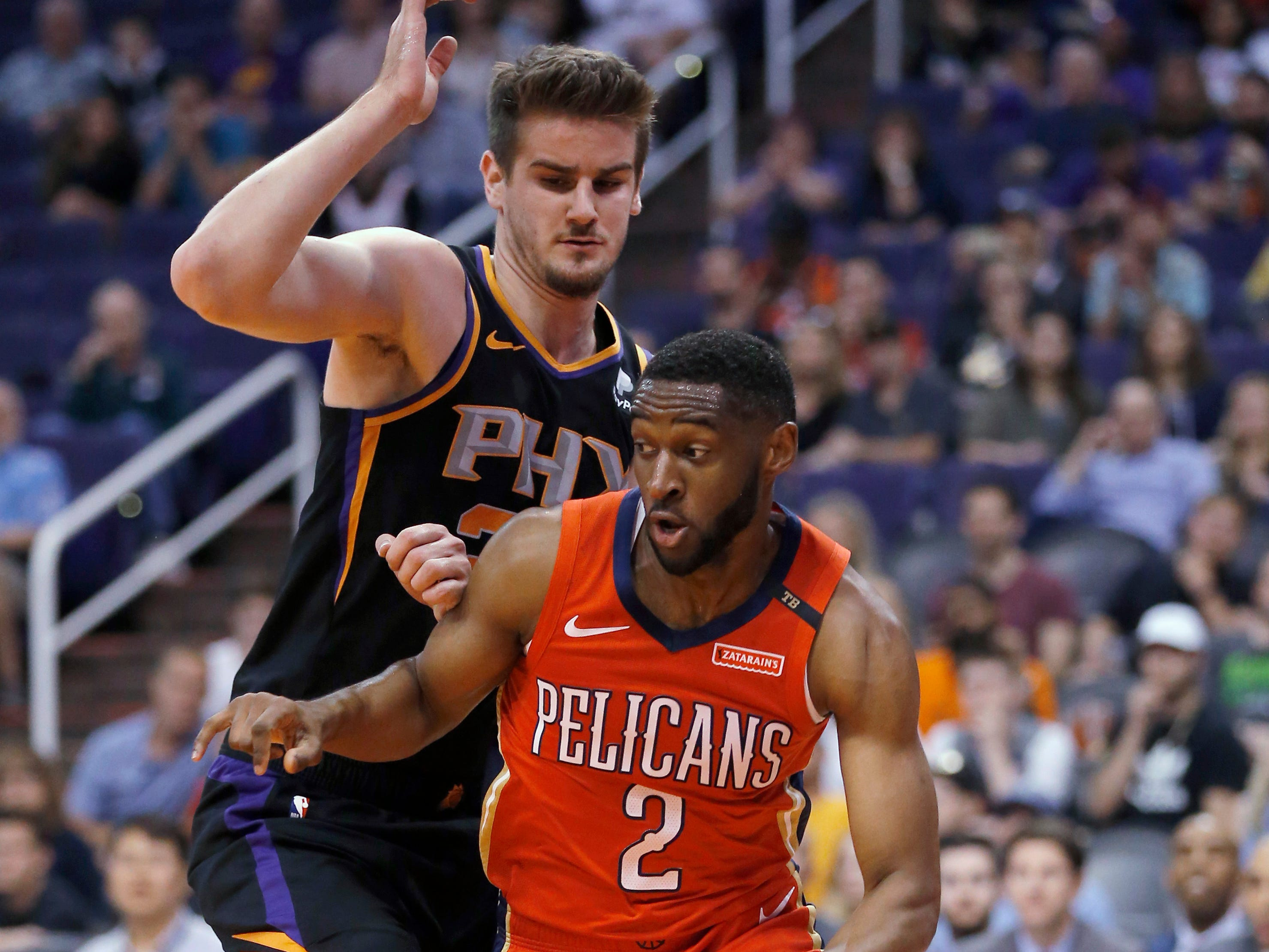 New Orleans Pelicans guard Ian Clark (2) drives past Phoenix Suns forward Dragan Bender during the first half of an NBA basketball game Friday, April 5, 2019, in Phoenix. (AP Photo/Rick Scuteri)