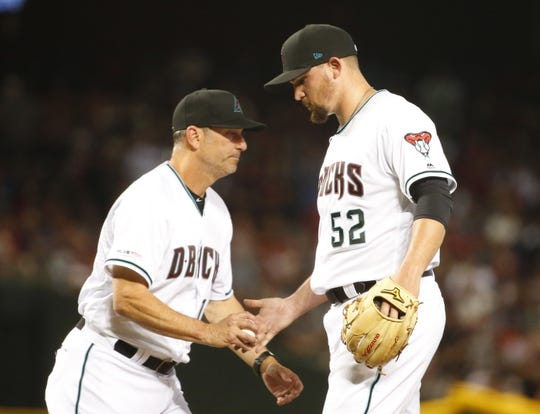 Arizona Diamondbacks manager Torey Lovullo (17) relieves  Arizona Diamondbacks starting pitcher Zack Godley (52) during the 6th inning of the Opening Day game against Boston Red Sox at Chase Field in Phoenix on April 5.