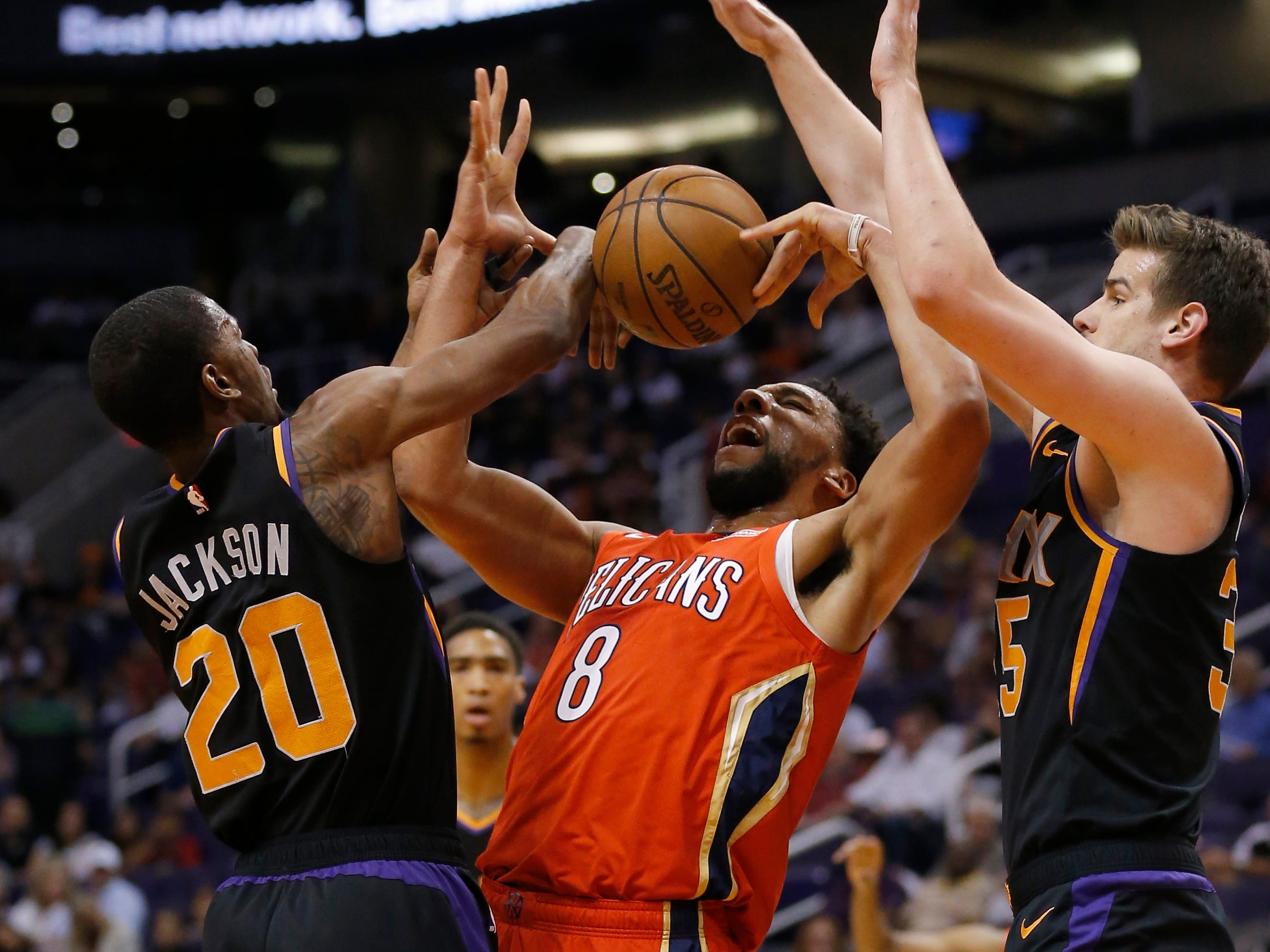 New Orleans Pelicans center Jahlil Okafor (8) battles for the loose ball with Phoenix Suns' Josh Jackson (20) and Dragan Bender during the first half of an NBA basketball game Friday, April 5, 2019, in Phoenix. (AP Photo/Rick Scuteri)