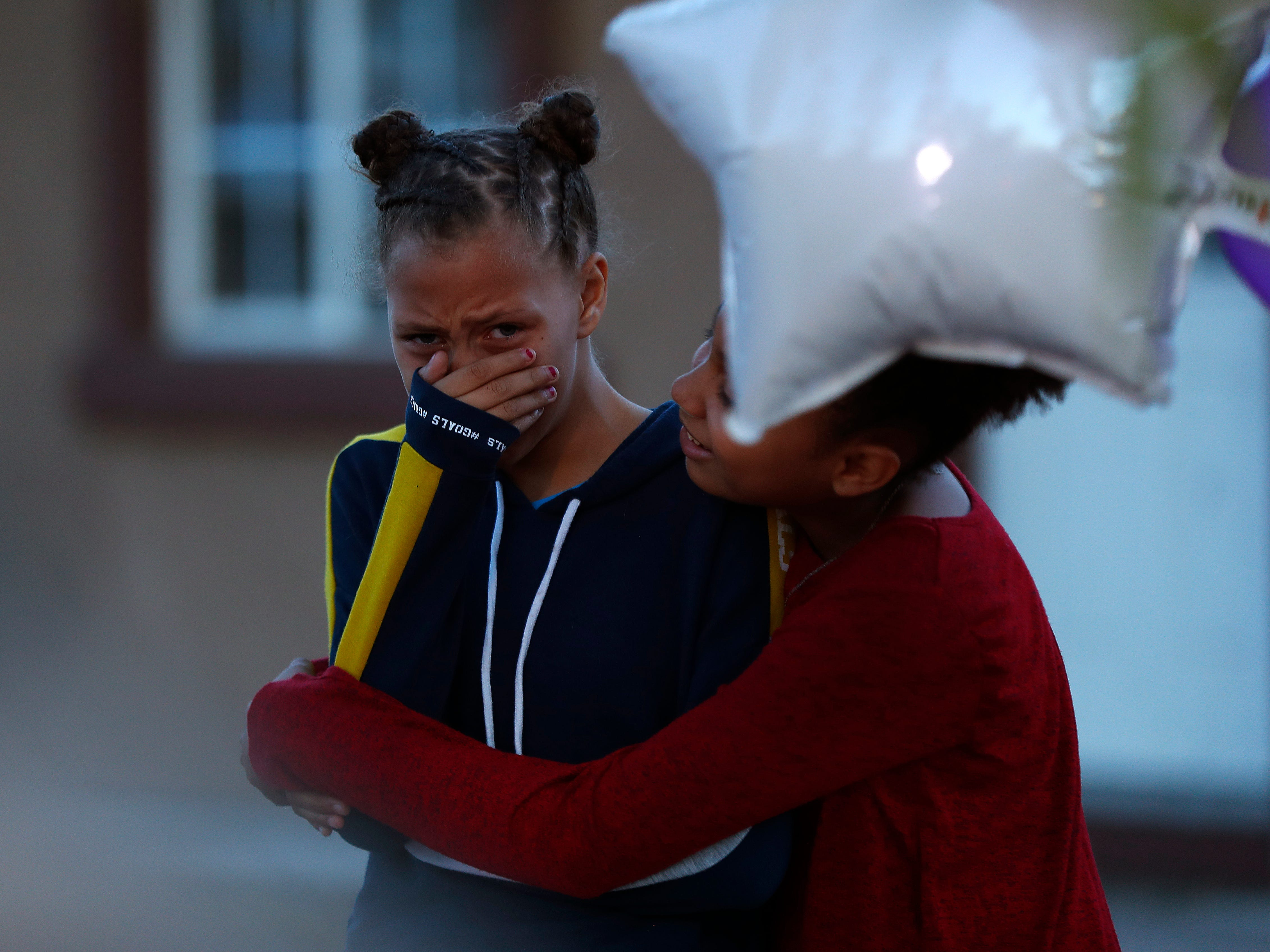 Naima hugs Lilly Hernandez as the two cry at a vigil for Summer Bell Brown on April 5, 2019, outside her home where she was shot and killed in Phoenix. Naima and Lilly were friends of Brown, who was 10 years old.