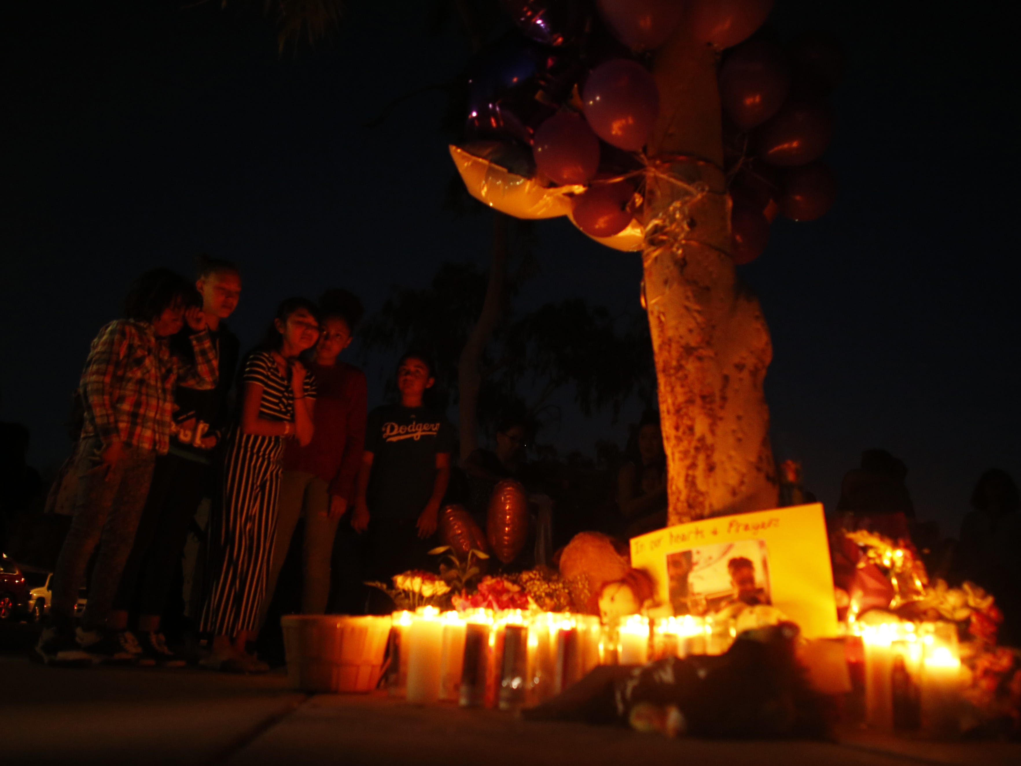 Classmates and friends cry as they gather around the candlelight at a vigil for Summer Bell Brown on April 5, 2019, outside her home where she was shot and killed in Phoenix. Brown was 10 years old.