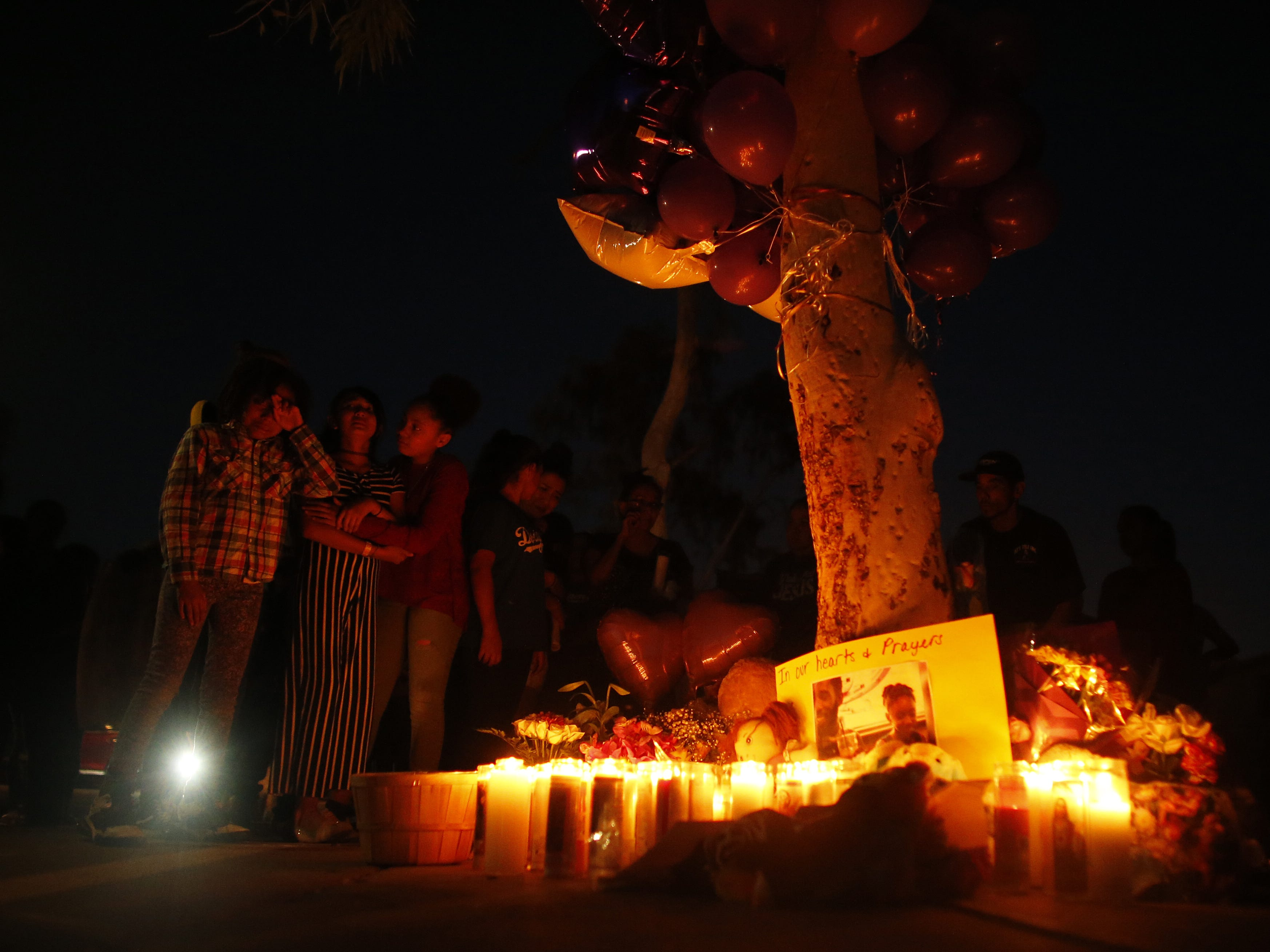 Jazlynn Boungert gets hugged by friends as they cry around the candlelight at a vigil for Summer Bell Brown on April 5, 2019, outside her home where she was shot and killed in Phoenix. Brown was 10 years old.