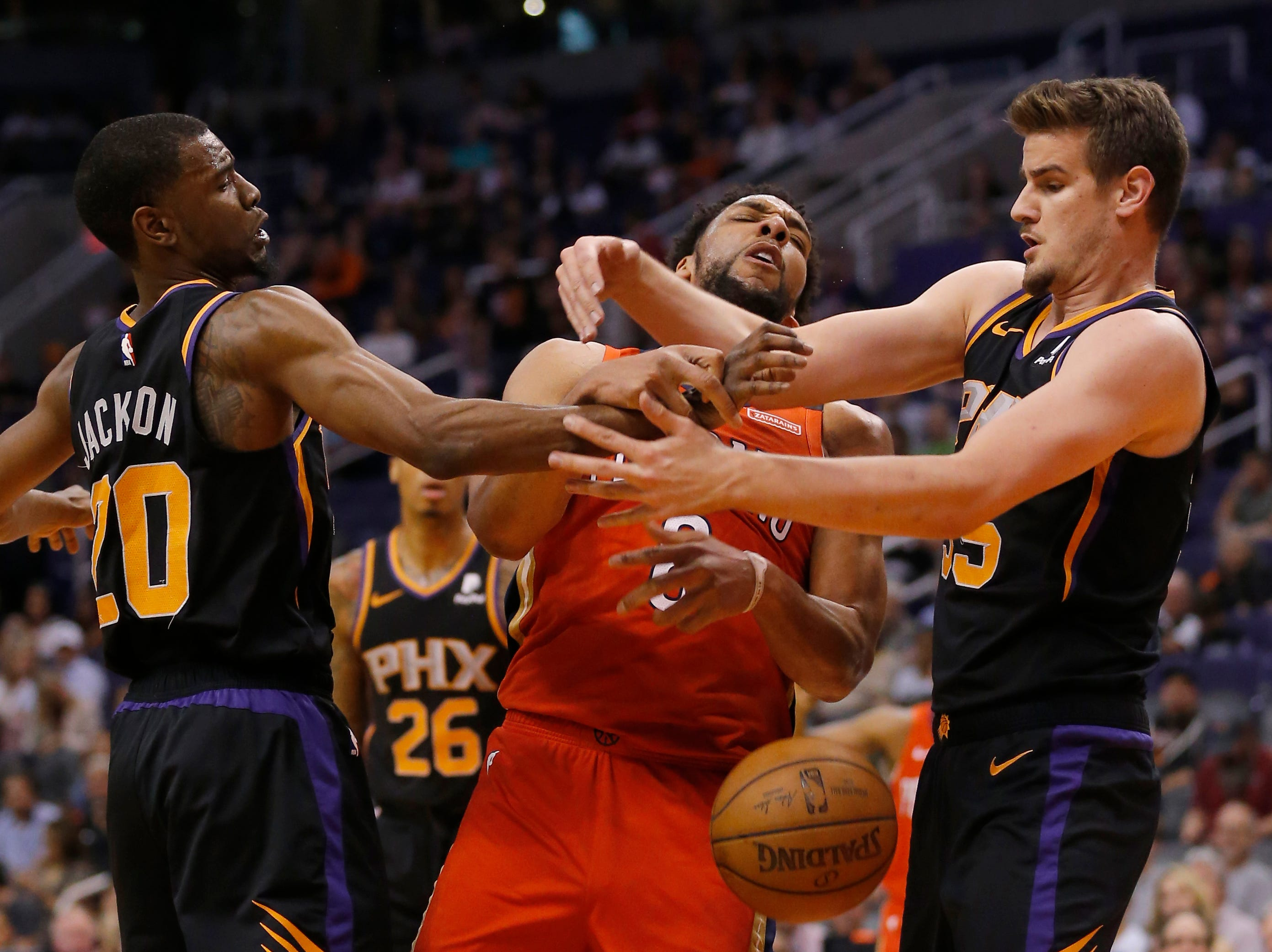 New Orleans Pelicans center Jahlil Okafor (8) battles for the loose ball with Phoenix Suns forward Josh Jackson (20) and Dragan Bender in the first half during an NBA basketball game, Friday, April 5, 2019, in Phoenix. (AP Photo/Rick Scuteri)