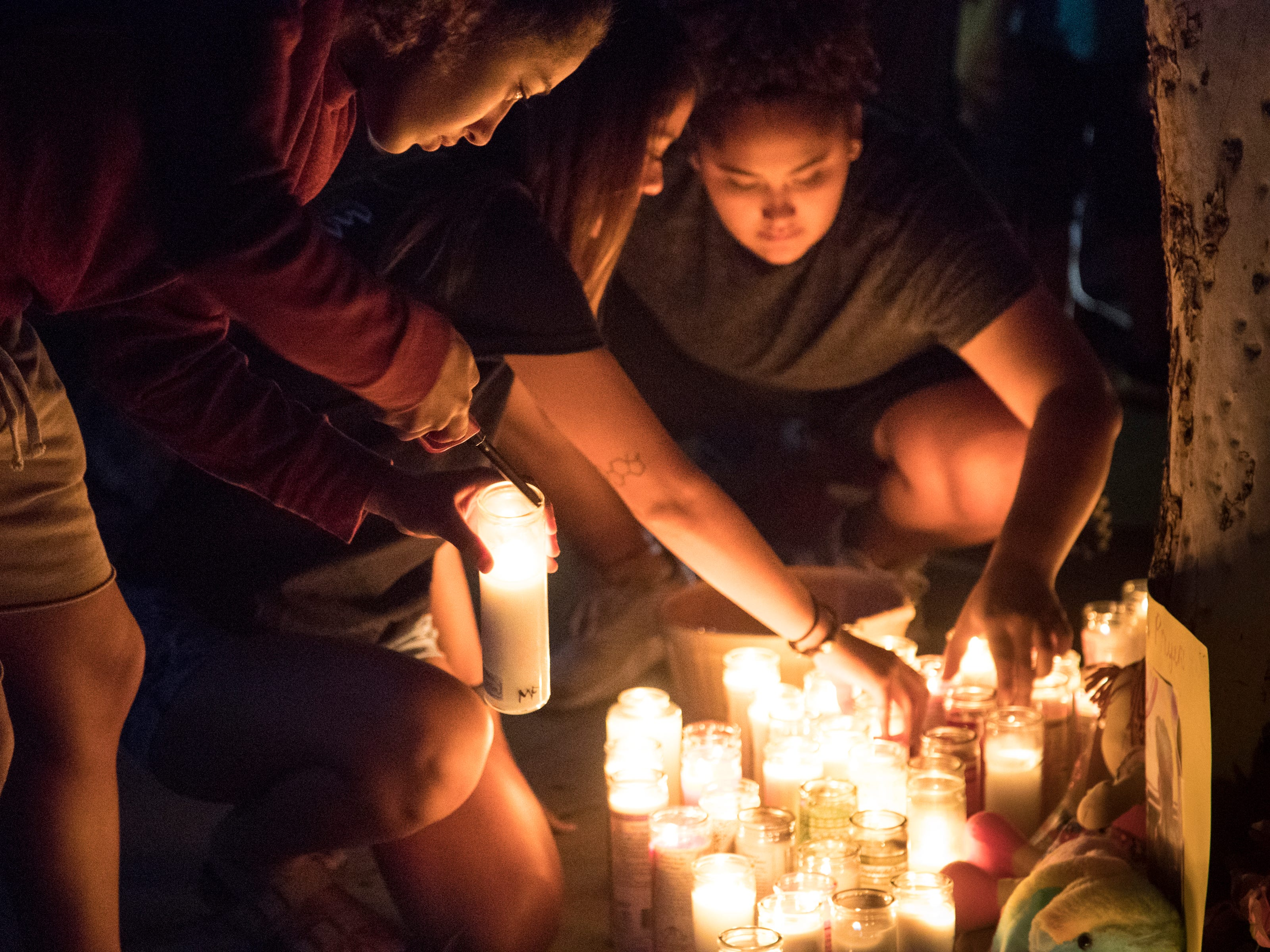 Jahleza Clark (left, family friend) and others light candles during a vigil for Summer Bell Brown on April 5, 2019.