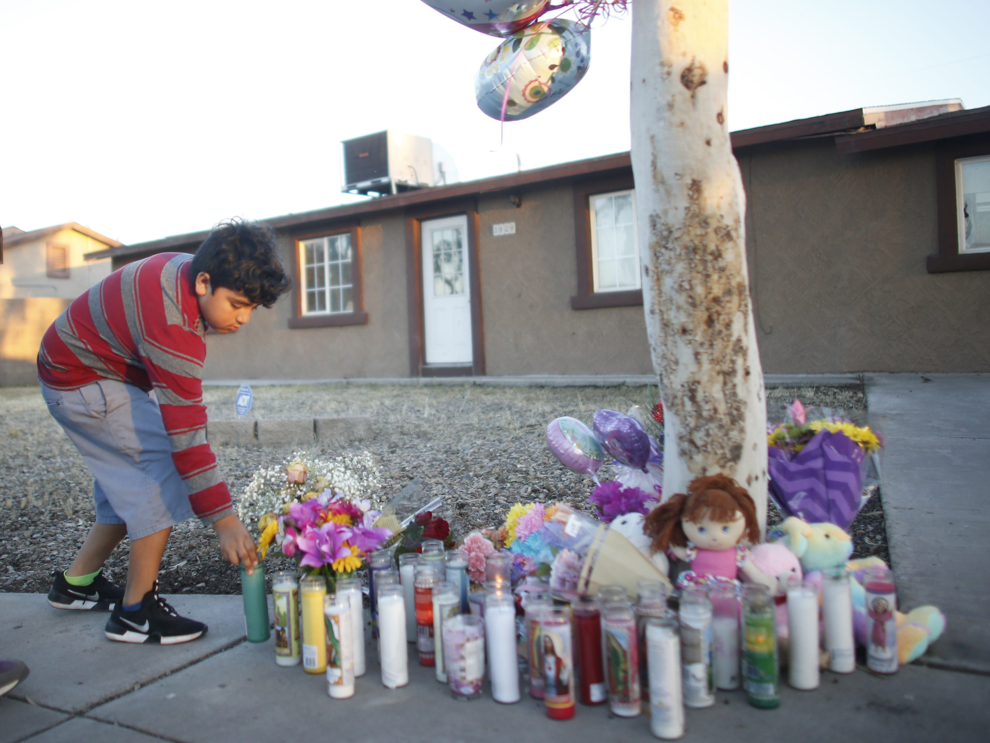 Jose Vargas places a candle at a vigil for Summer Bell Brown on April 5, 2019, outside her home where she was shot and killed in Phoenix.