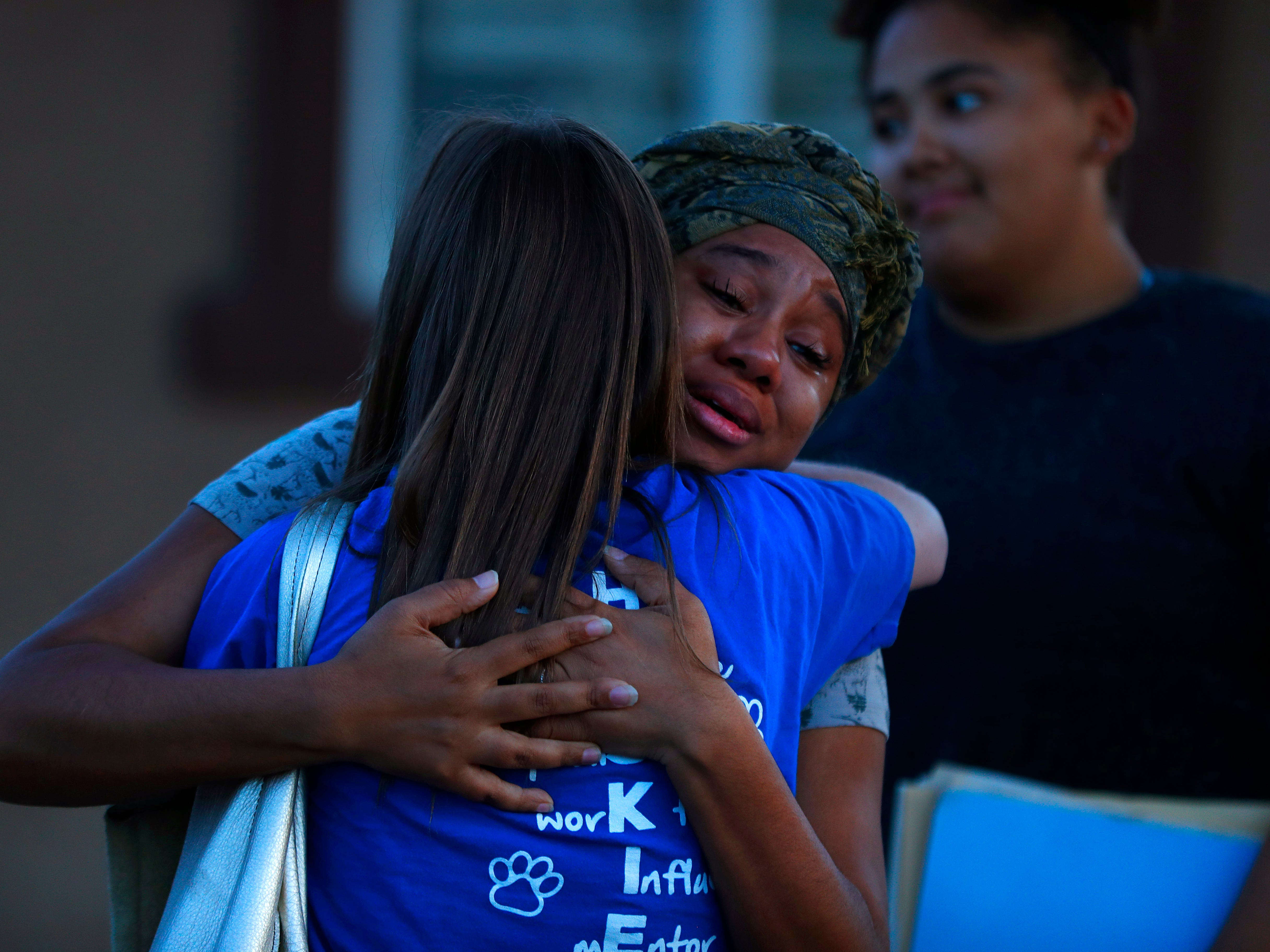 Taniesha Brown hugs her daughter's fourth-grade teacher at a vigil for Summer Bell Brown on April 5, 2019, outside her home where she was shot and killed in Phoenix. Summer was 10 years old.