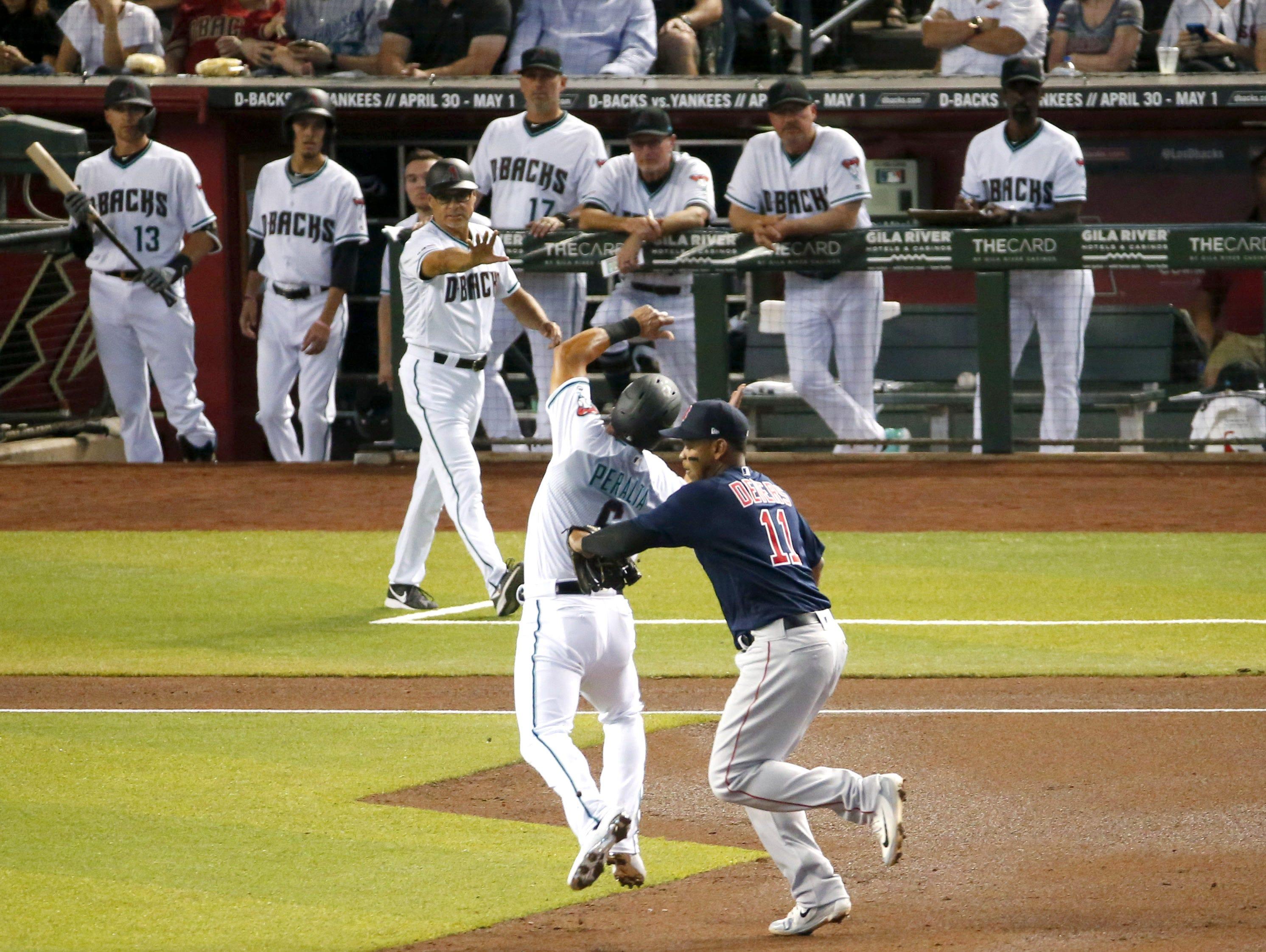 Boston Red Sox third baseman Rafael Devers (11) outs Arizona Diamondbacks right fielder David Peralta (6) during Opening Day at Chase Field in Phoenix on April 5.