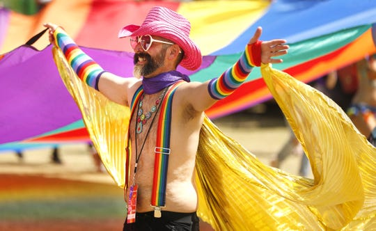 Jim Nowlin dances around with a giant Pride flag during Phoenix Pride at Steele Indian School Park on April 6, 2019.