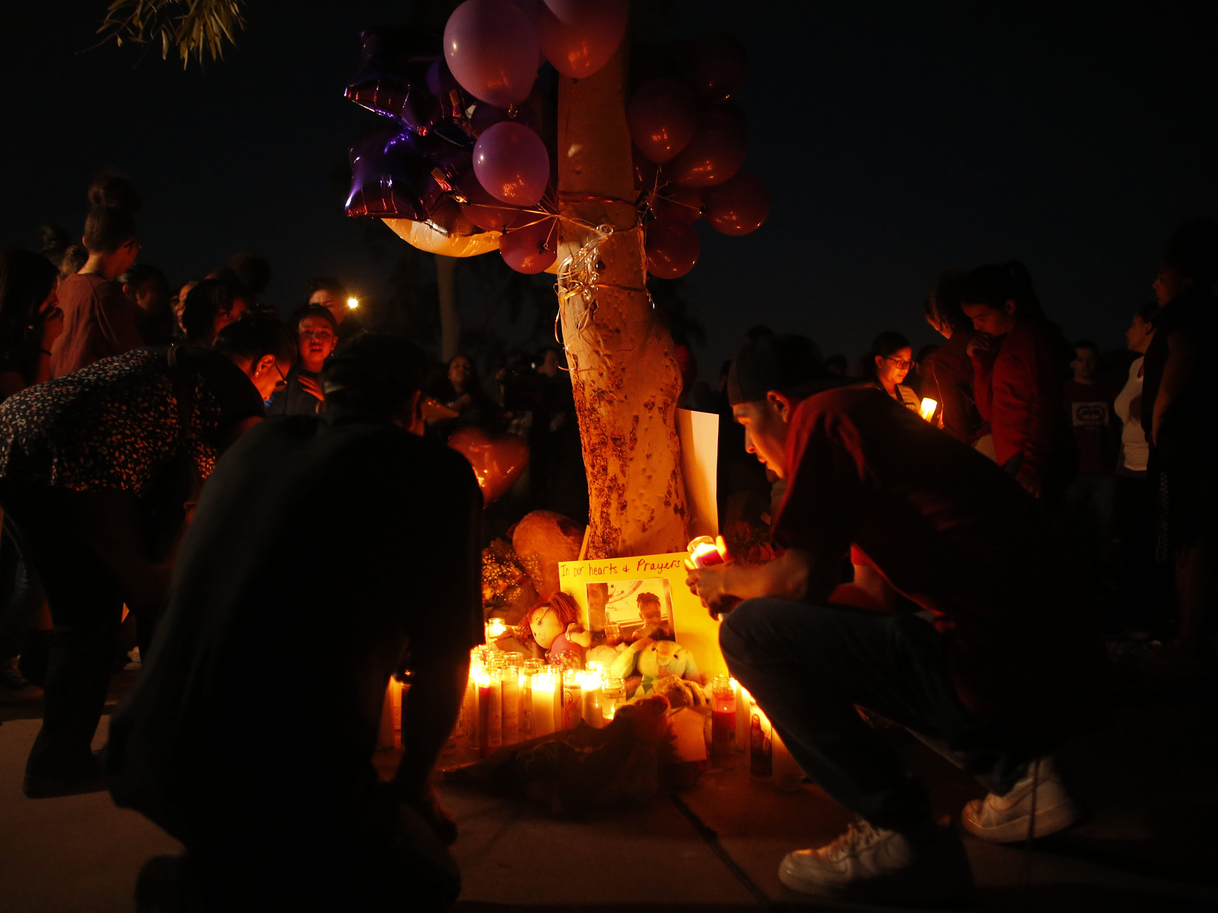 People place candles at a vigil for Summer Bell Brown on April 5, 2019, outside her home where she was shot and killed in Phoenix. Brown was 10 years old.