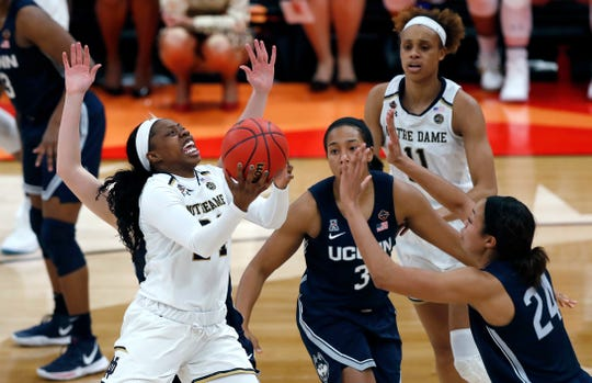 Notre Dame guard Arike Ogunbowale, left, goes up for a shot against Connecticut guard Megan Walker (3) and forward Napheesa Collier (24) during the second half of a Final Four semifinal of the NCAA women's college basketball tournament Friday, April 5, 2019, in Tampa, Fla. (AP Photo/Mark LoMoglio)
