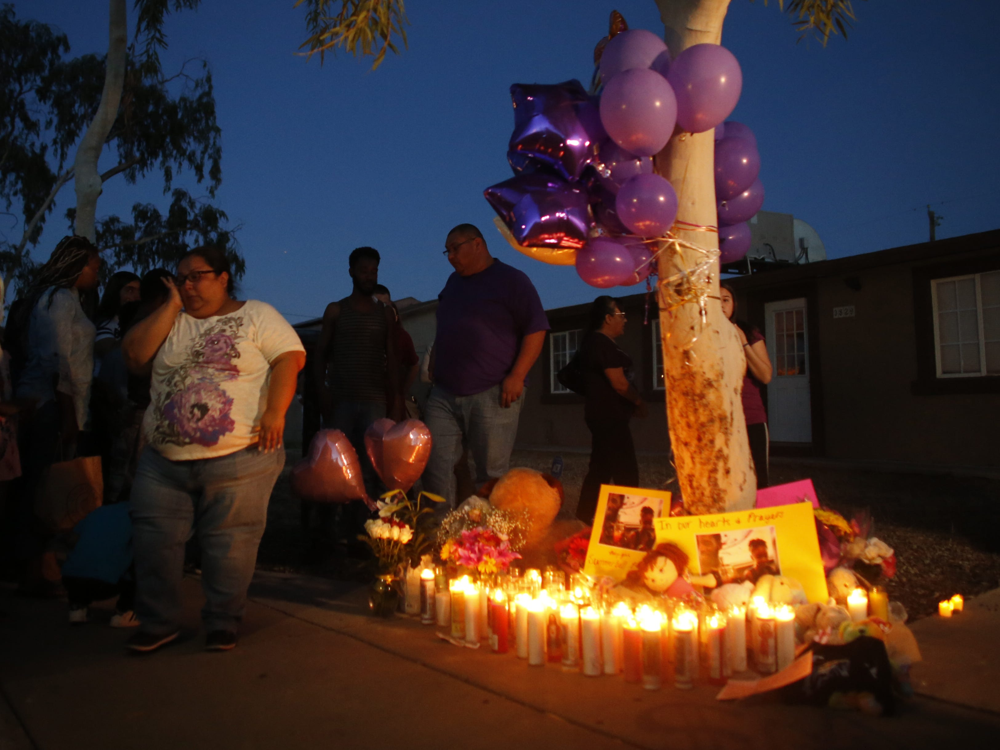 Candles glow as the sun sets at a vigil for Summer Bell Brown on April 5, 2019, outside her home where she was shot and killed in Phoenix.