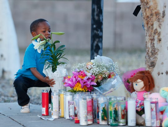 RJ Green, a sibling of a classmate and friend, walks flowers to a vigil for Summer Bell Brown on April 5, 2019, outside her home where she was shot and killed in Phoenix.
