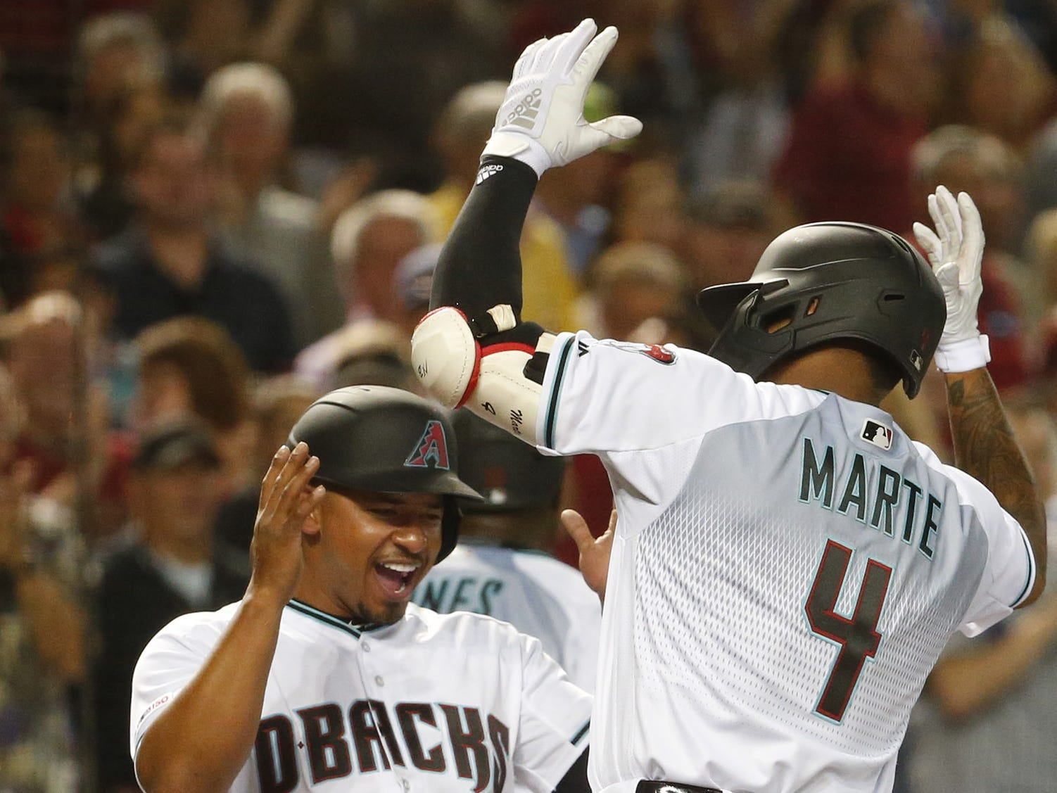 Arizona Diamondbacks third baseman Eduardo Escobar (5) celebrates shortstop Ketel Marte's (4) grand slam in the sixth inning of a Opening Day game at Chase Field in Phoenix on April 5.