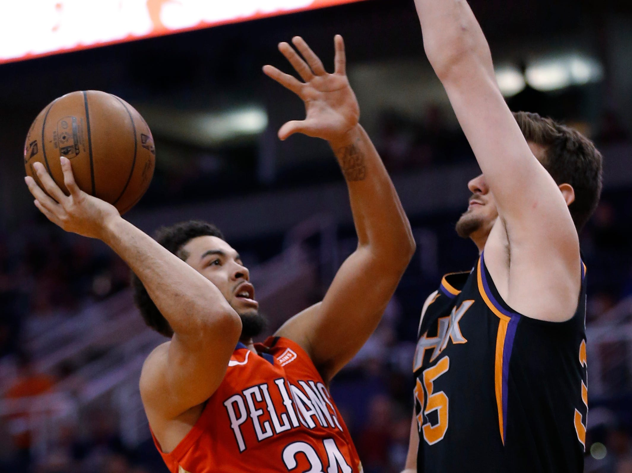 New Orleans Pelicans guard Kenrich Williams (34) drives on Phoenix Suns forward Dragan Bender during the first half of an NBA basketball game Friday, April 5, 2019, in Phoenix. (AP Photo/Rick Scuteri)