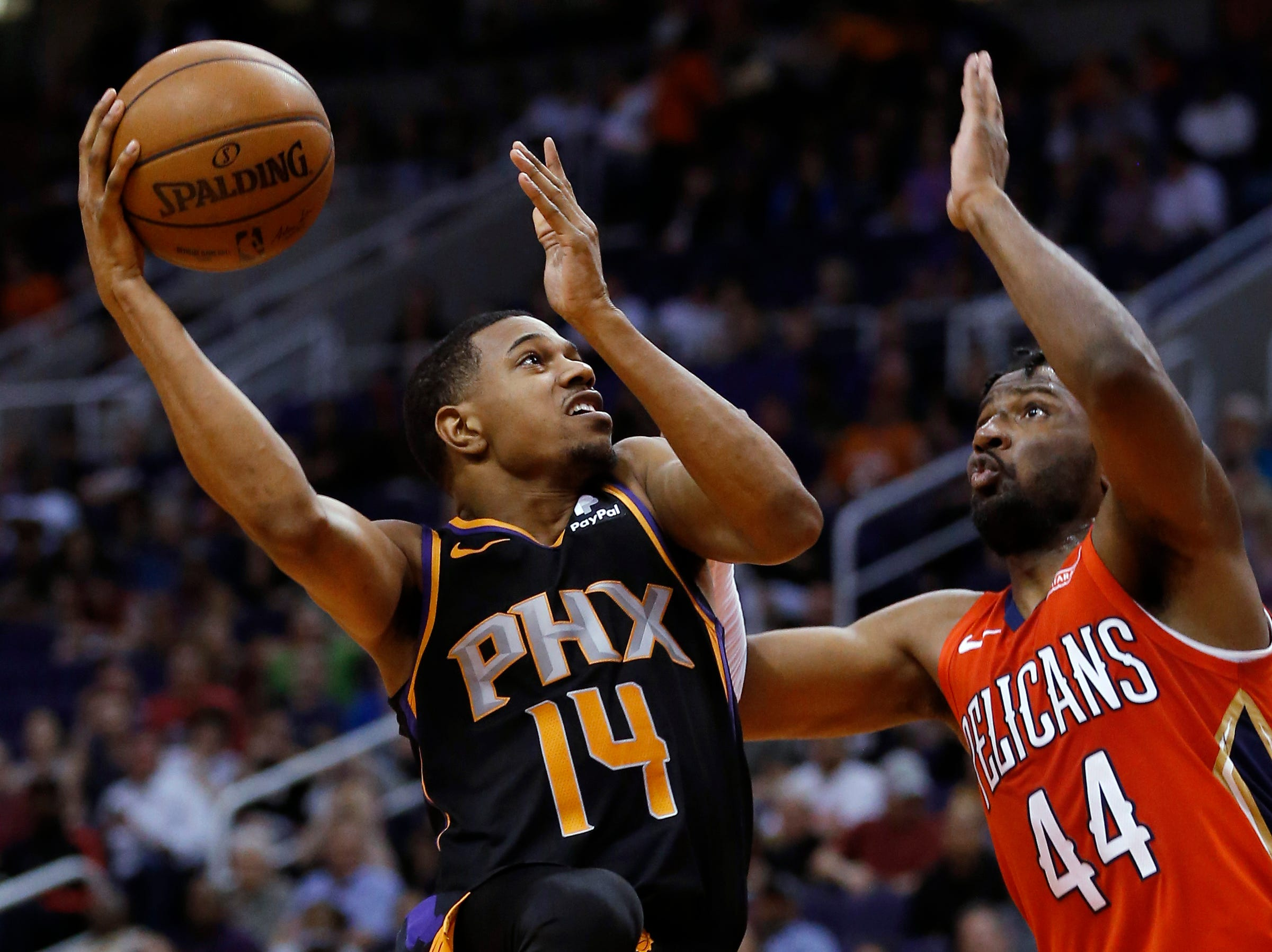 Phoenix Suns guard De'Anthony Melton (14) shoots over New Orleans Pelicans forward Solomon Hill during the second half of an NBA basketball game Friday, April 5, 2019, in Phoenix. The Suns won 133-126 in overtime. (AP Photo/Rick Scuteri)