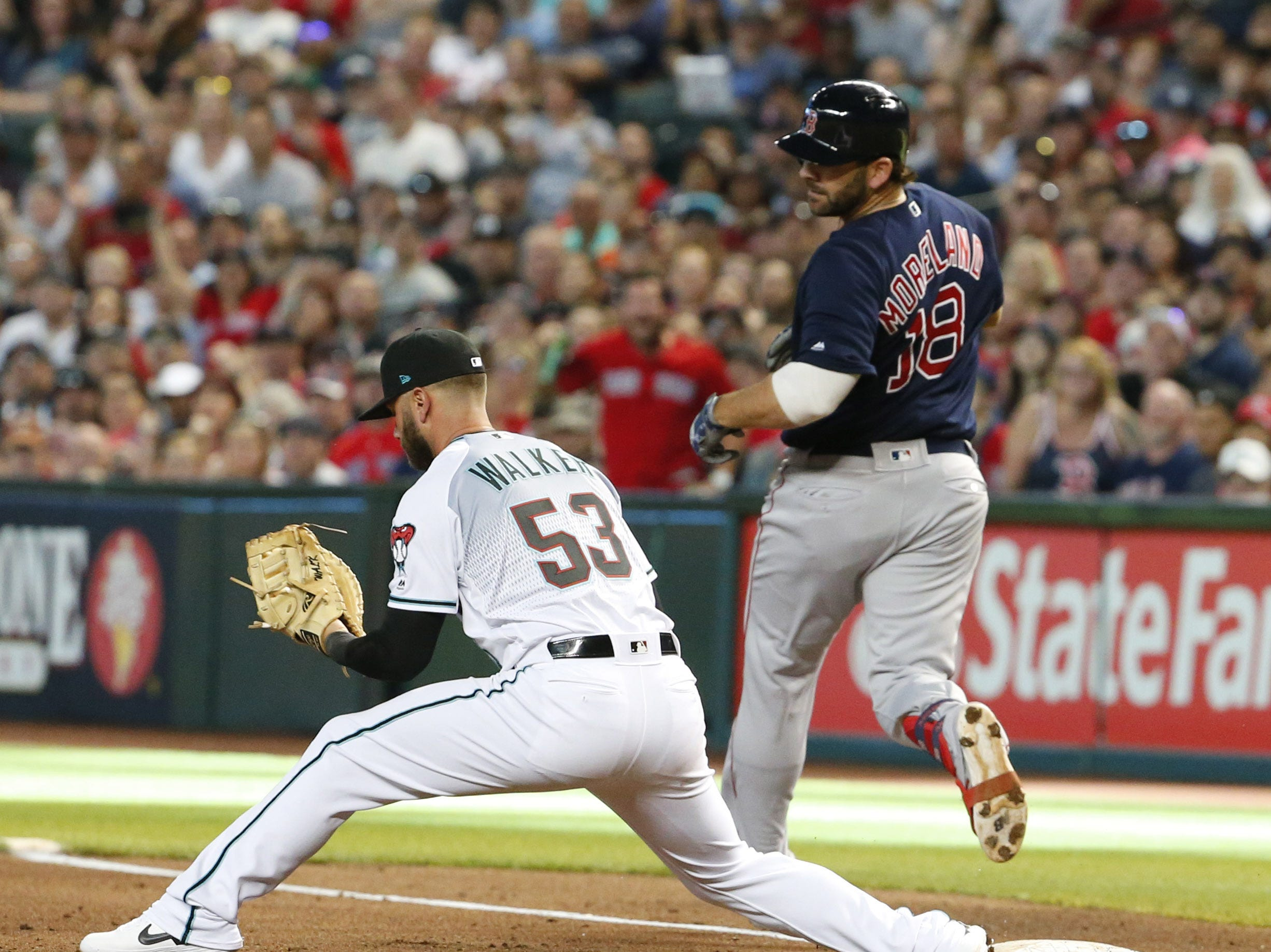 Arizona Diamondbacks first baseman Christian Walker (53) outs Boston Red Sox first baseman Mitch Moreland (18) during a MLB Opening Day game at Chase Field in Phoenix on April 5.