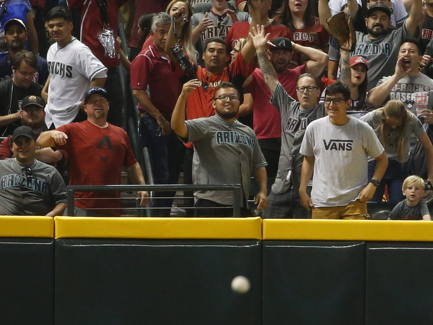 A Arizona Diamondbacks fan throws a Boston Red Sox home run ball back on the field during Opening Day game at Chase Field in Phoenix on April 5.