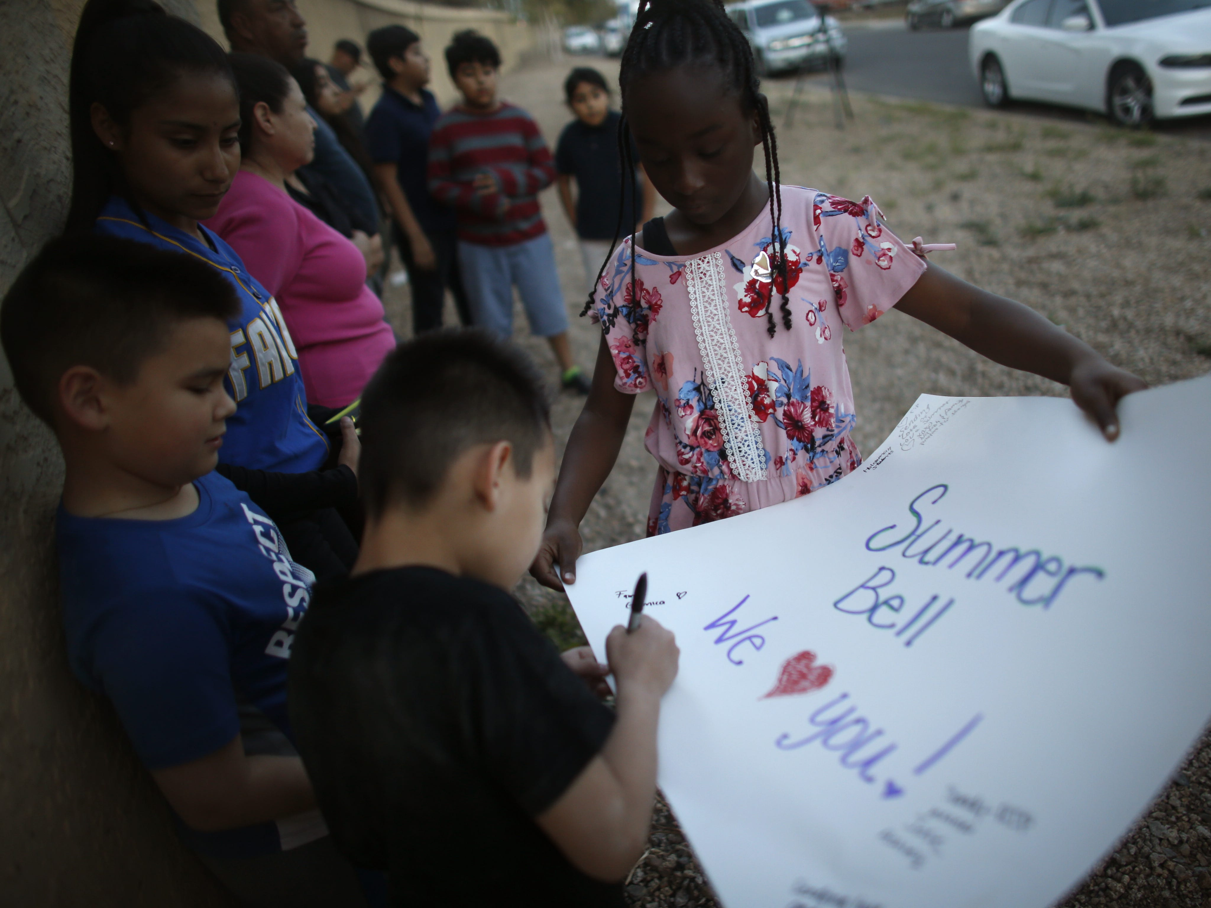 """Narija Anthony, 8, has children sign a poster saying """"Summer Bell We Heart You"""" at a vigil for Summer Bell Brown on April 5, 2019, outside her home where she was shot and killed in Phoenix."""