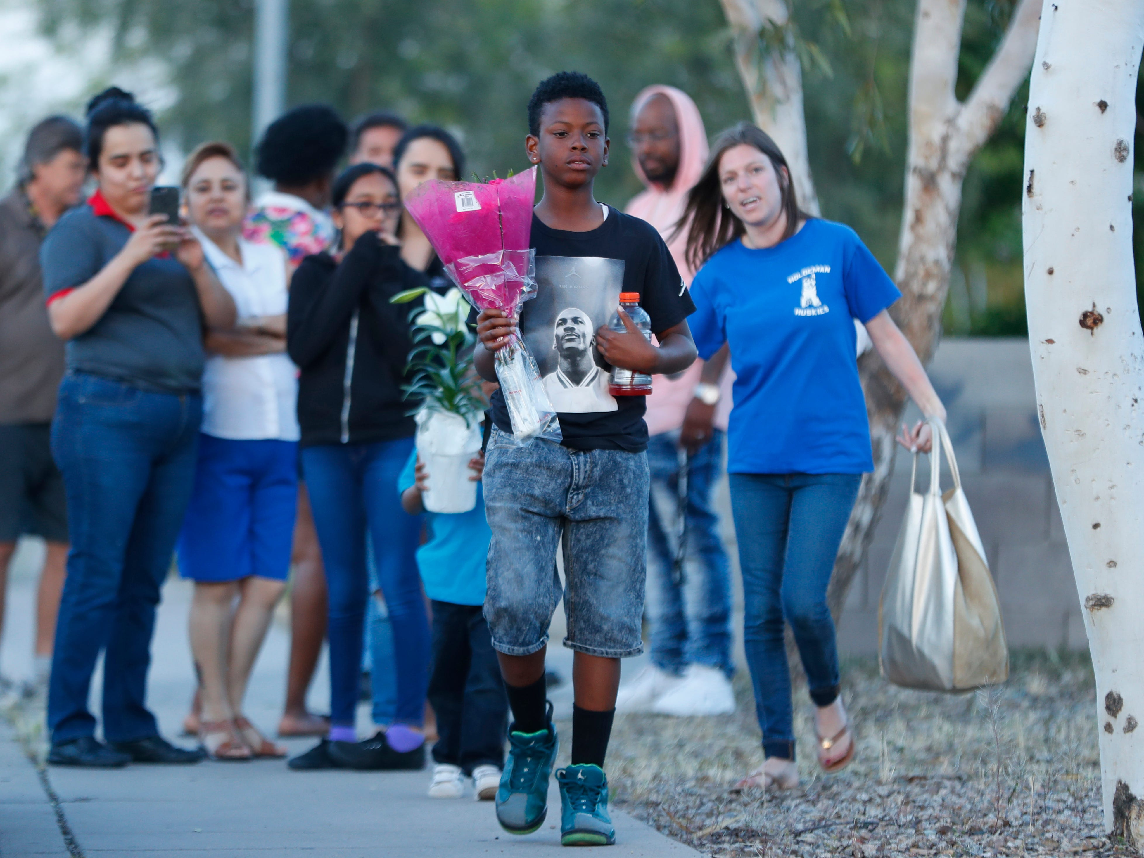 Kameron Green, a classmate and friend, walks as he carries flowers for a vigil for Summer Bell Brown on April 5, 2019, held outside her home where she was shot and killed in Phoenix.