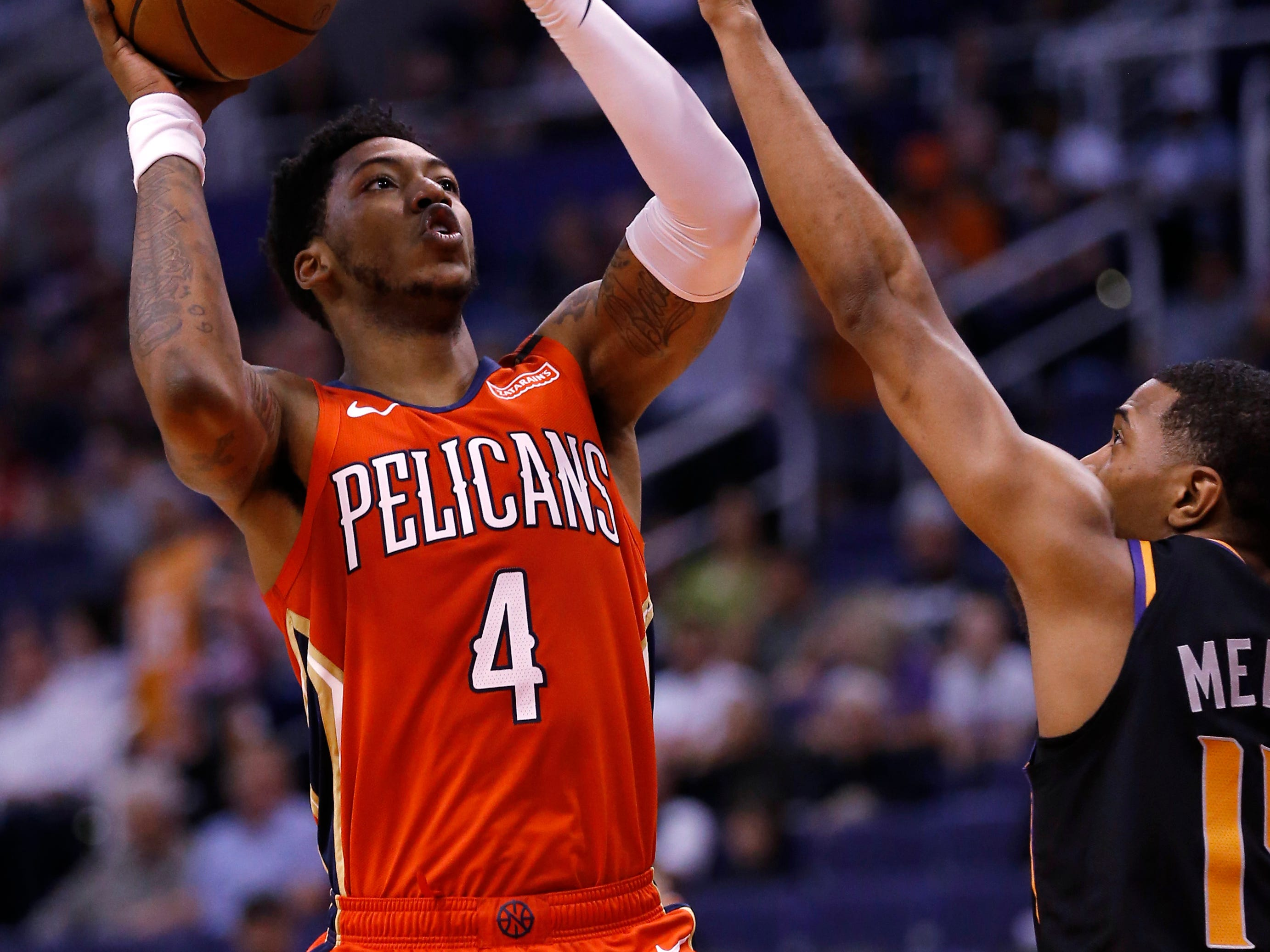 New Orleans Pelicans guard Elfrid Payton (4) shoots over Phoenix Suns guard De'Anthony Melton during the first half of an NBA basketball game Friday, April 5, 2019, in Phoenix. (AP Photo/Rick Scuteri)