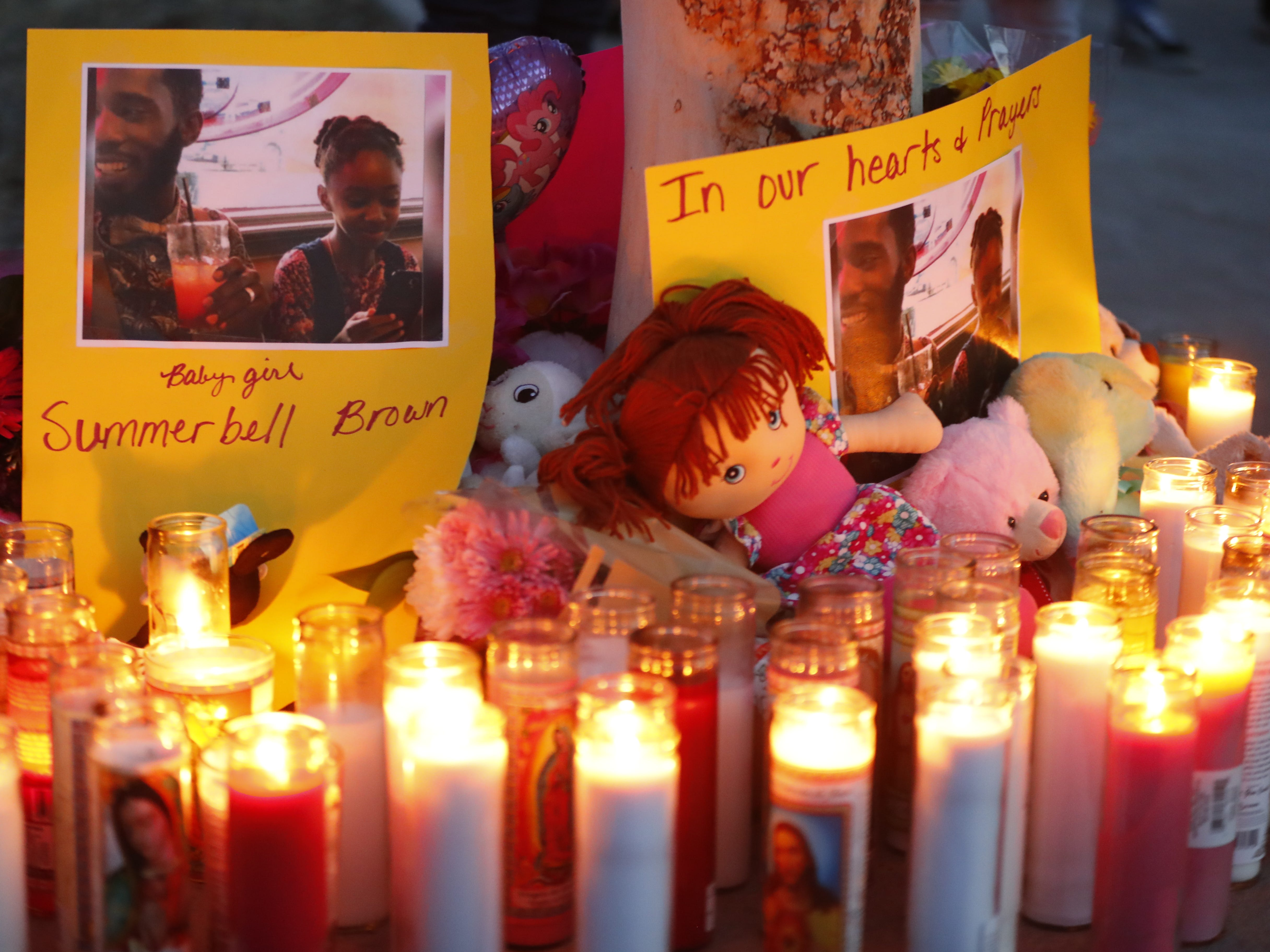 Candles illuminate posters at a vigil for Summer Bell Brown on April 5, 2019, outside her home where she was shot and killed in Phoenix. Brown was 10 years old.