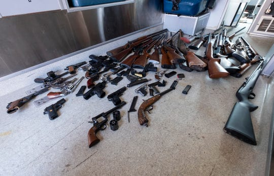Unloaded firearms purchased by the Port Huron Police Department during its gun buy-back program Saturday, April 6, 2019 are spread out on the floor in the back of a police vehicle.