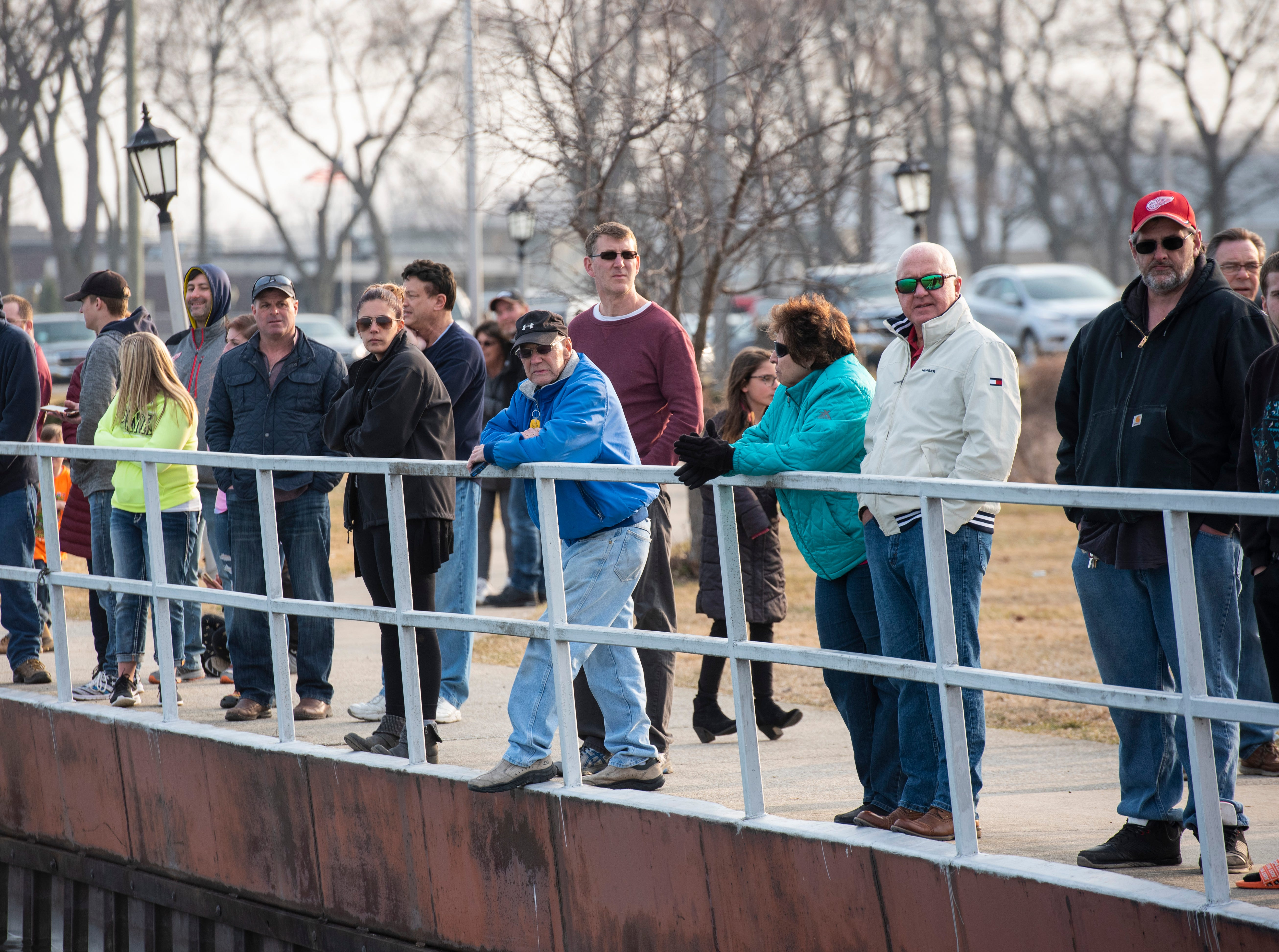 Spectators watch from a nearby boardwalk as crews work to remove a car from the St. Clair River near Junction Buoy in Marysville Saturday, April 6, 2019. The driver went to adjust the parking of the vehicle, and it rolled into the river. The vehicle floated down the river a ways before it and the driver went under. The driver later died.