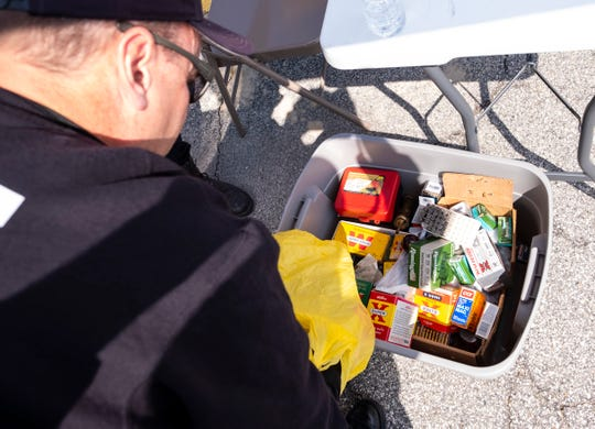 Port Huron Police Lt. Roger Wesch looks through a container full of ammunition taken in by the department during its gun buy-back program Saturday, April 6, 2019.