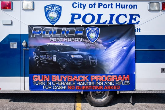 A banner for the Port Huron Police Department's gun buy-back program hangs on the side of a police vehicle during the event Saturday, April 6, 2019. During the event, the department purchased unwanted firearms, which will be sent to the Michigan State Police and destroyed.